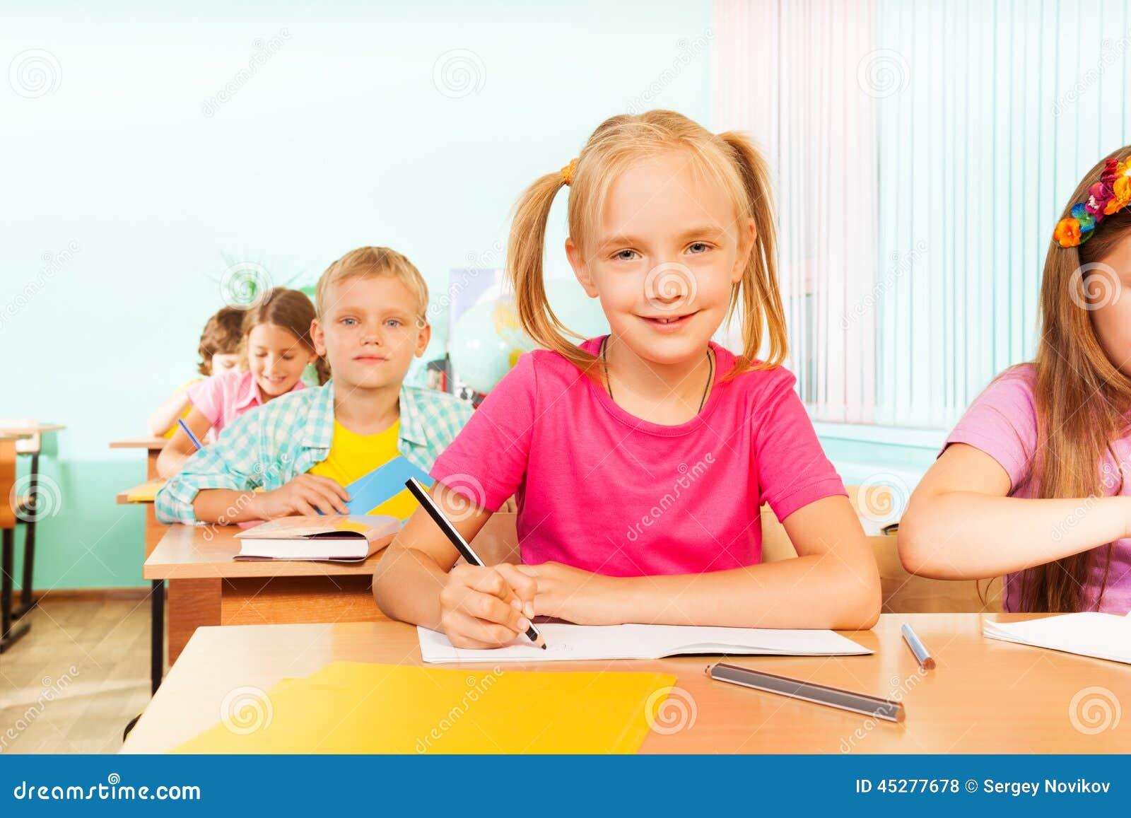 Jonge geitjes die bij lijst in klaslokaal en het schrijven zitten