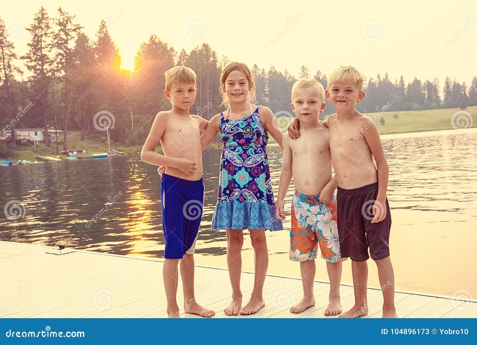 Jonge geitjes die de zomer van vakantie genieten bij het meer