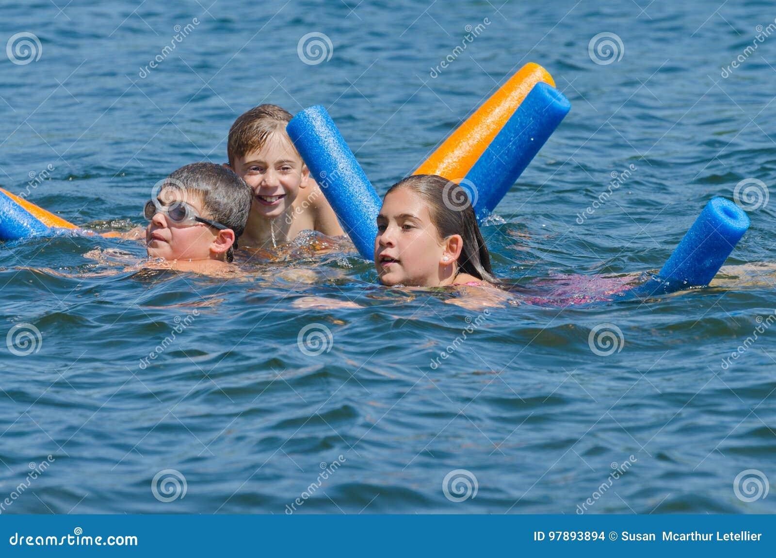 Jonge geitjes die de zomerpret hebben die in meer zwemmen