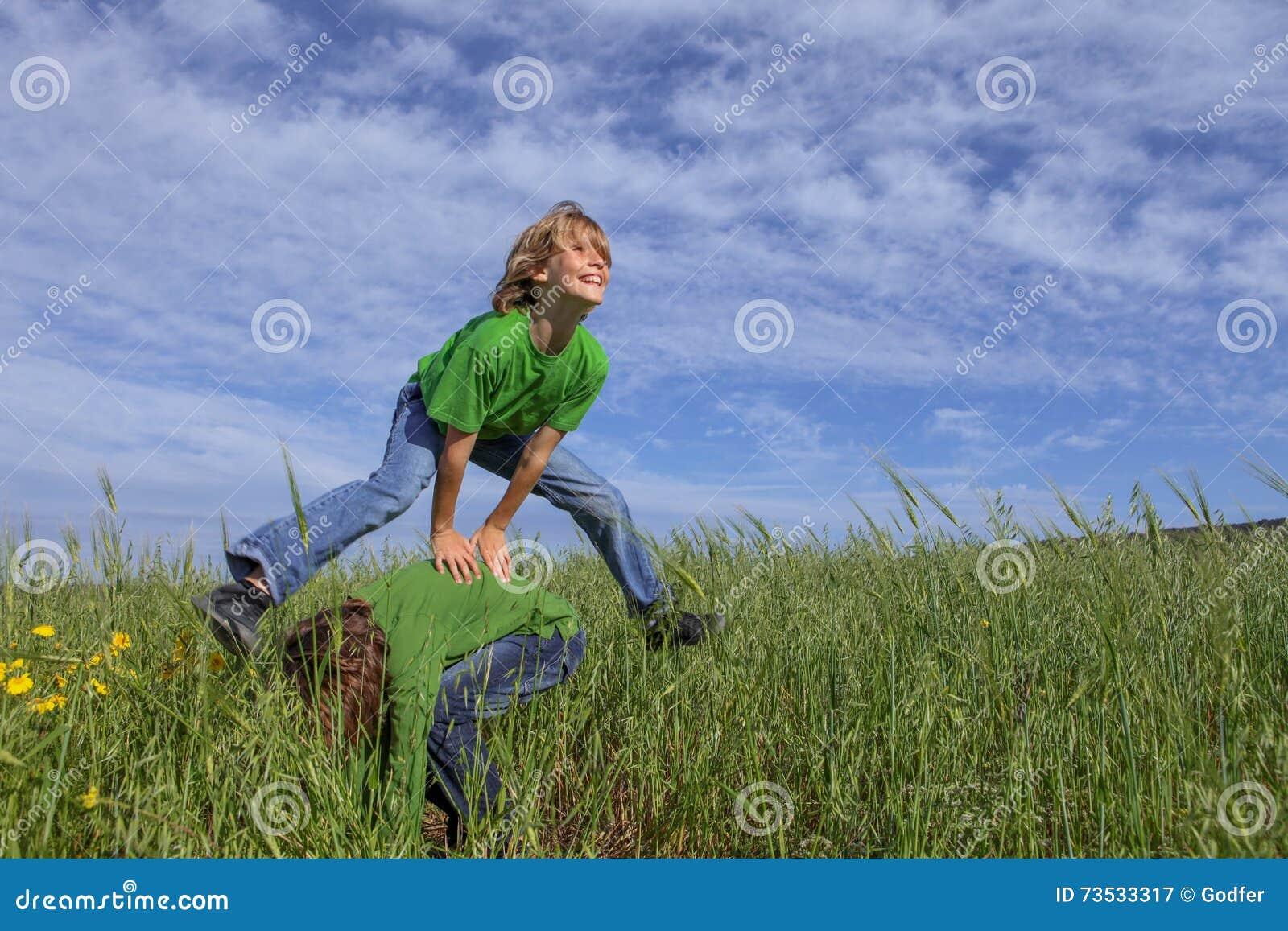 Jonge geitjes die leapfrog de zomerspel spelen