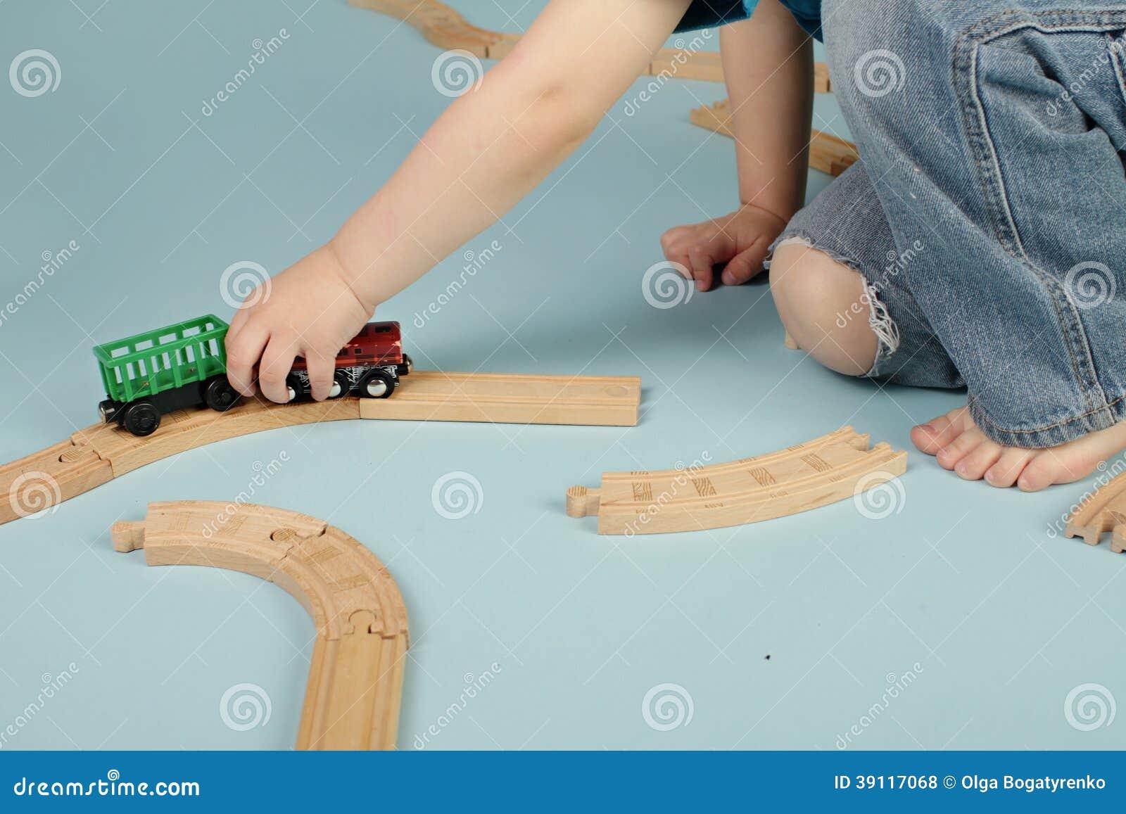 Jonge geitjes die met stuk speelgoed treinen spelen