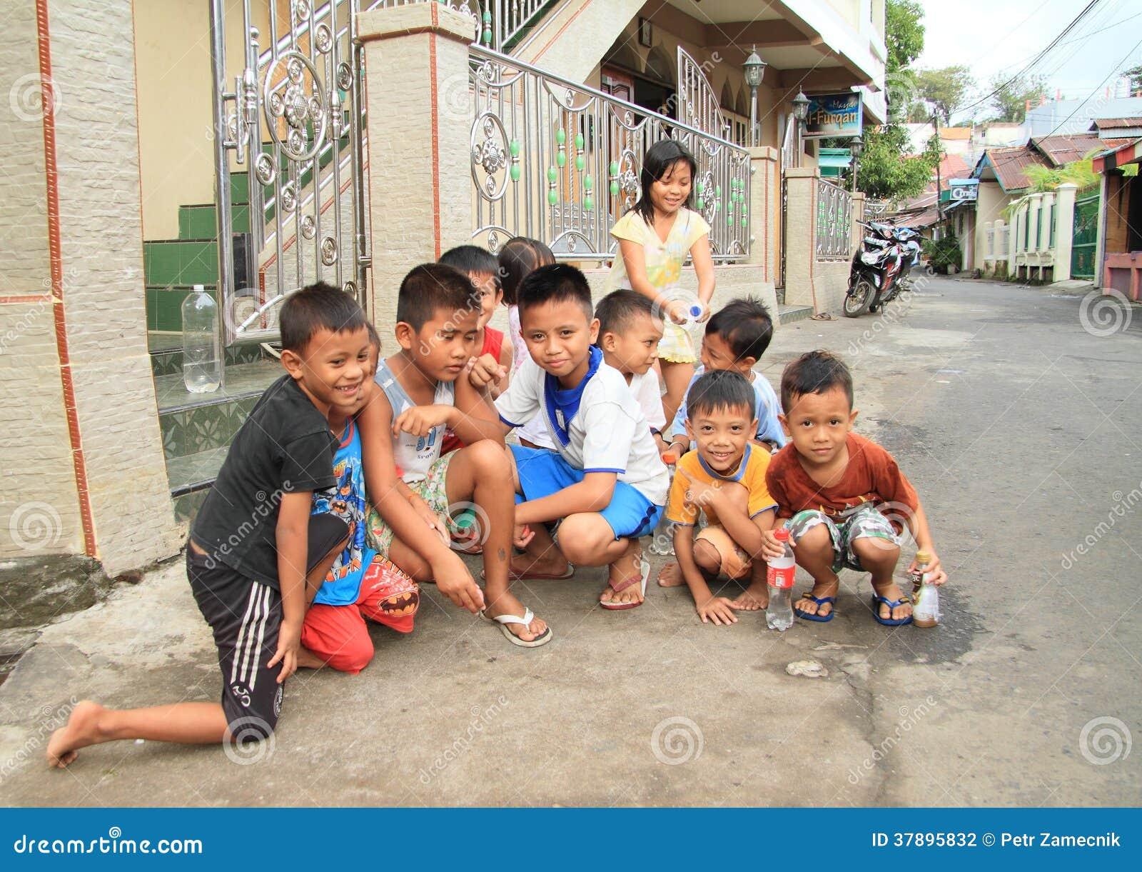 Jonge geitjes die op straat van Manado spelen
