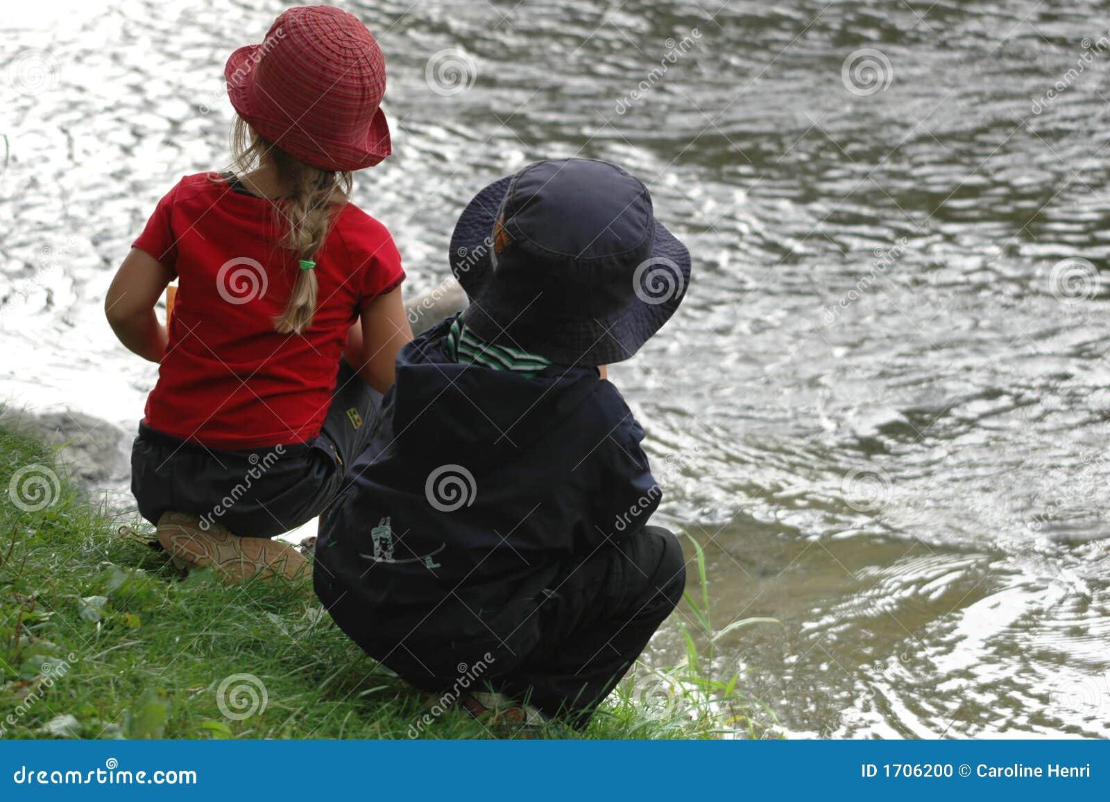 Jonge geitjes die rivier kijken