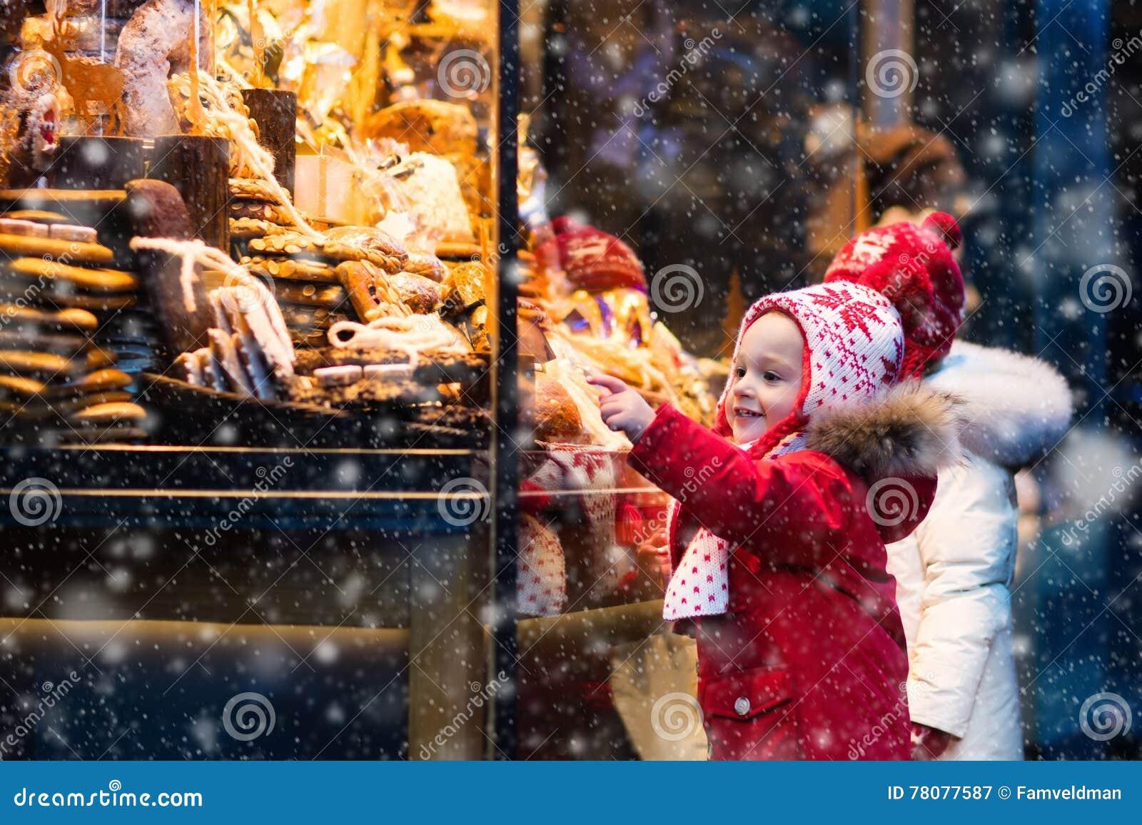 Jonge geitjes die suikergoed en gebakje op Kerstmismarkt bekijken