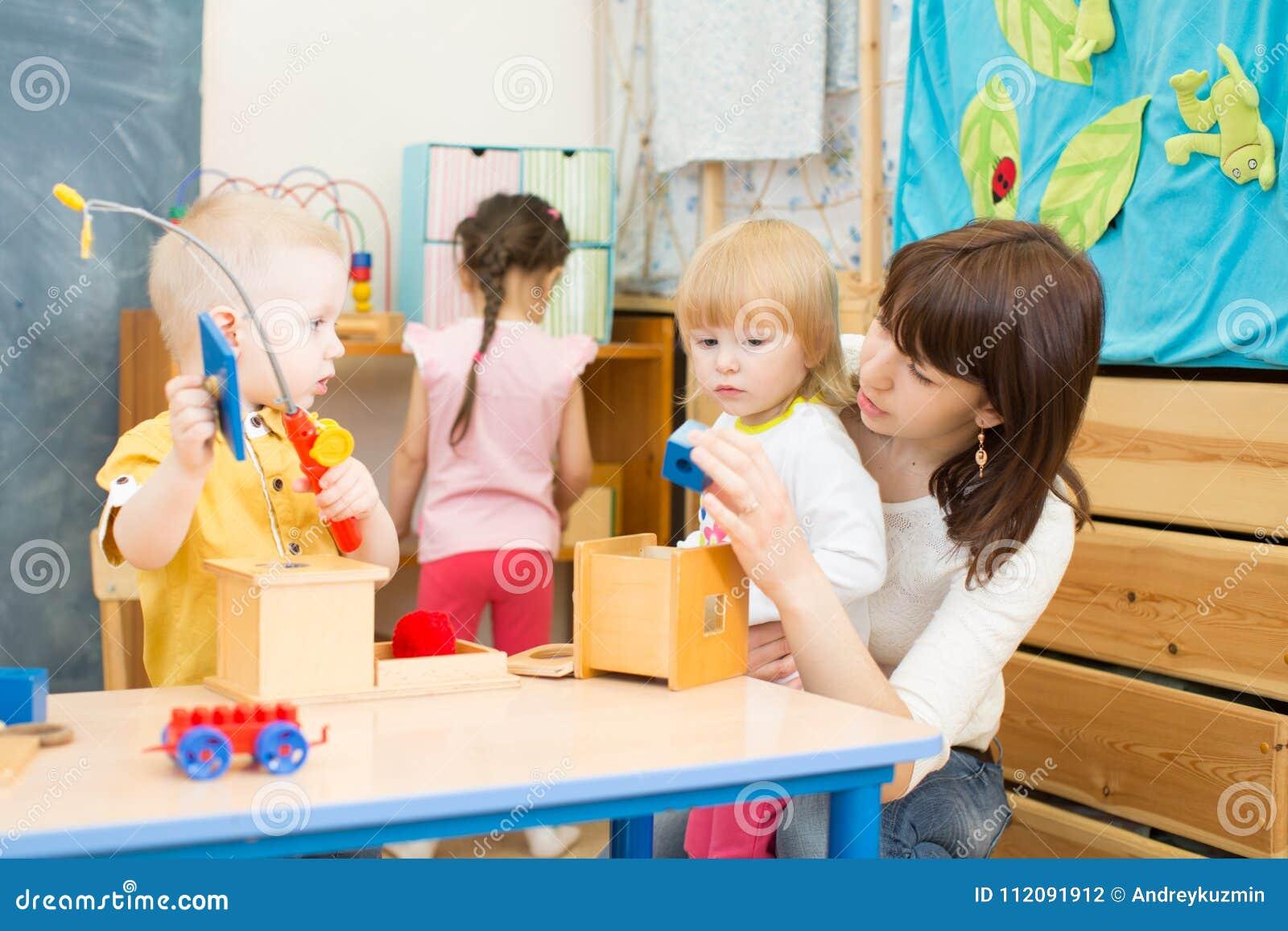 Jonge geitjesgroep het spelen met leraar in de speelkamer van het opvangcentrum