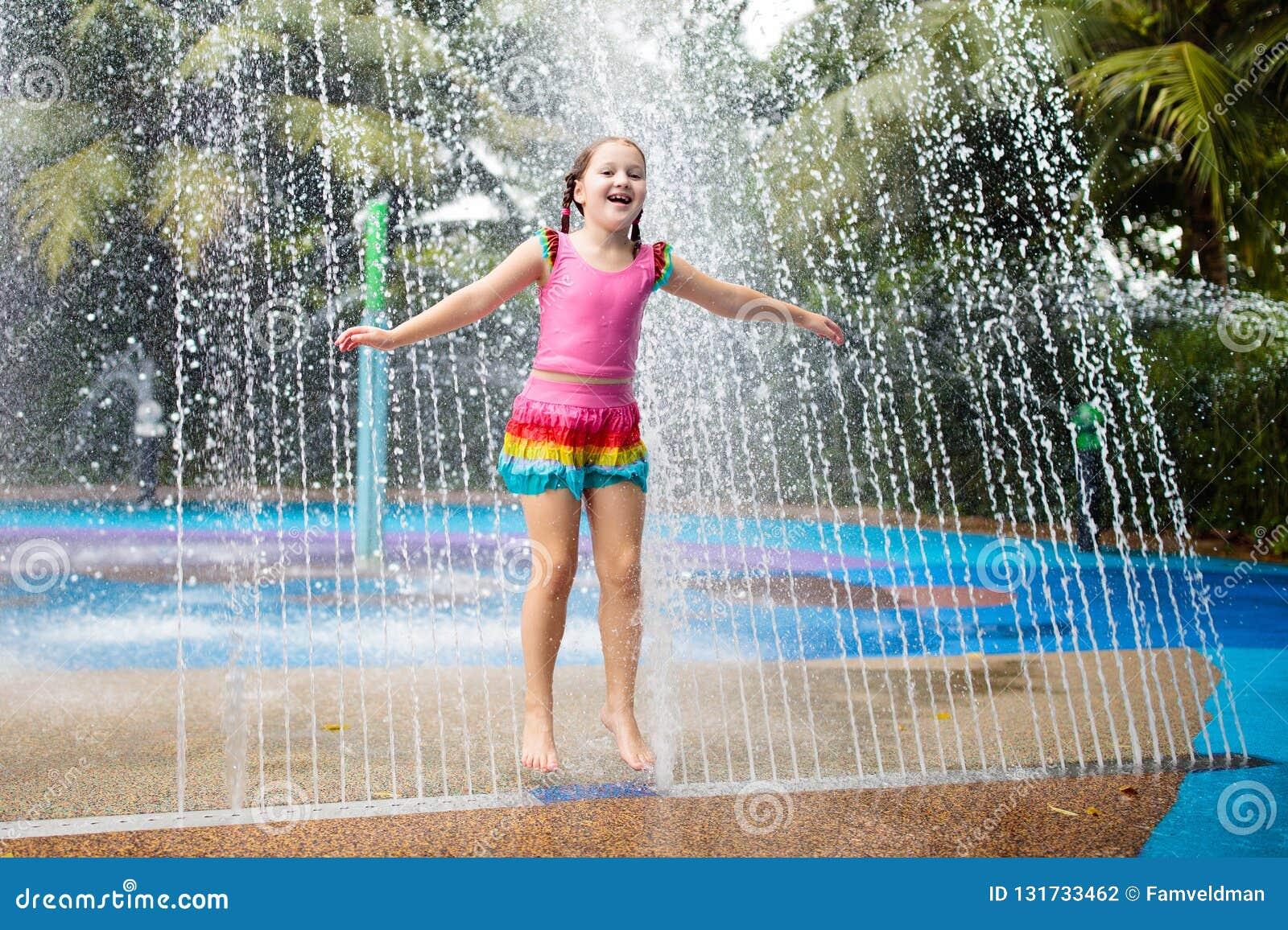 Jonge geitjesspel in aquapark Kinderen bij waterspeelplaats van tropisch pretpark Meisje bij zwembad