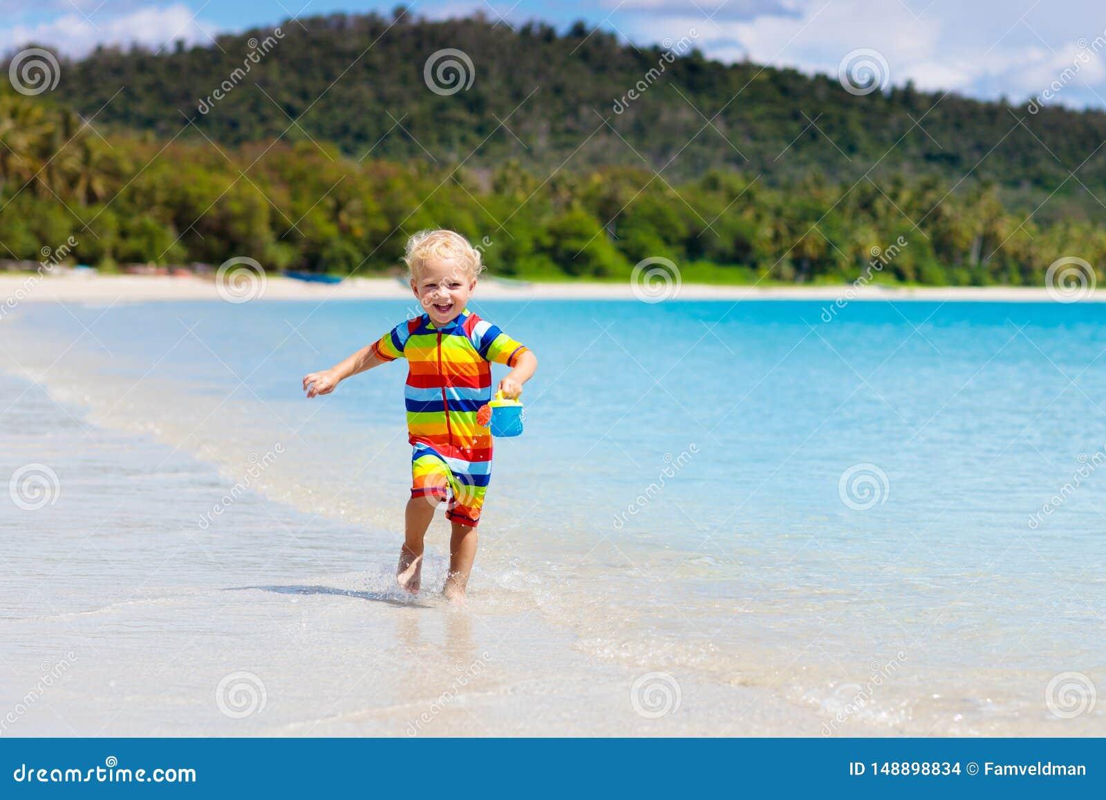 Jonge geitjesspel op tropisch strand Zand en waterstuk speelgoed