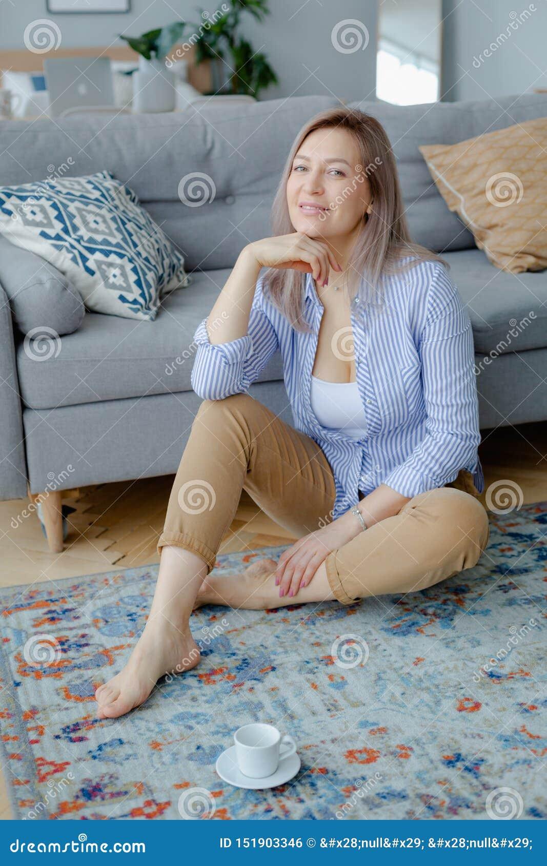 Jonge gelukkige blondevrouw in comfortabel binnenland
