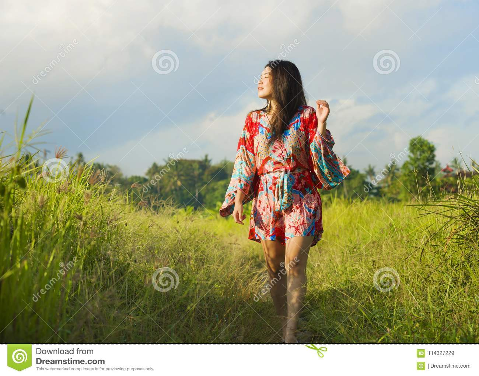 Jonge gelukkige en speelse Aziatische Chinese vrouw in mooie kleding die pret hebben die vakantie van excursie op gras tropisch g