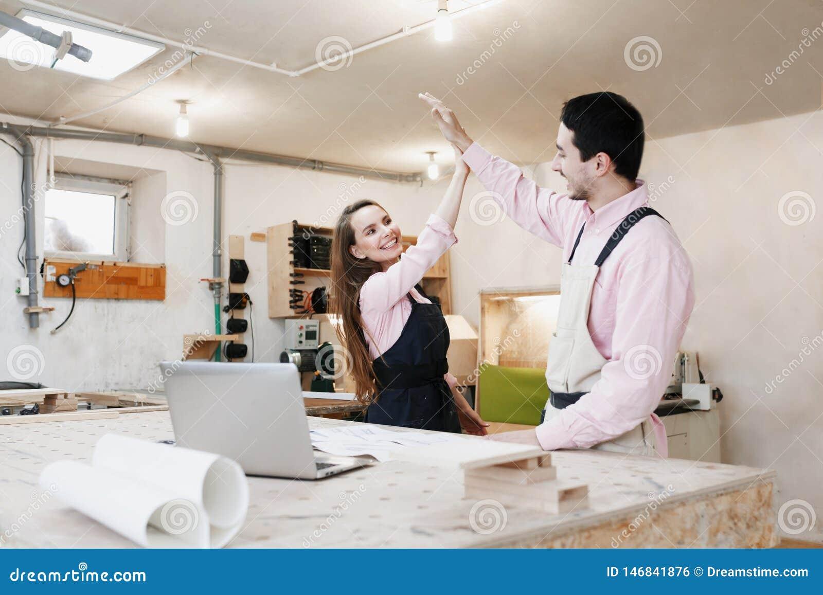 Jonge gelukkige familie die zich bij een het werkbank bevinden in een timmerwerkworkshop, die een project schrijven Familiebedrij