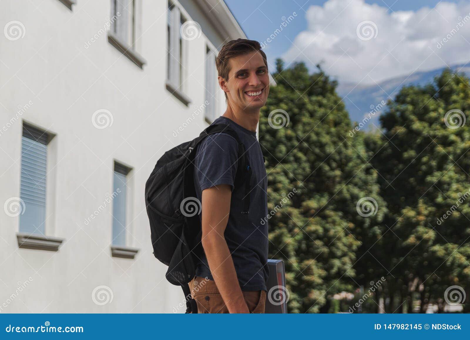 Jonge gelukkige mens die met rugzak aan school na de zomervakantie lopen
