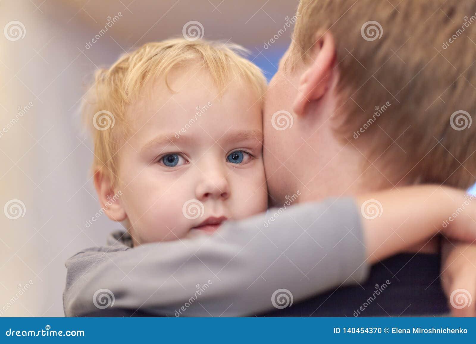 Jonge gelukkige mens die zijn leuke zoon houden De babyjongen omhelst de mannelijke hals Ernstig weinig jong geitje met blauwe og