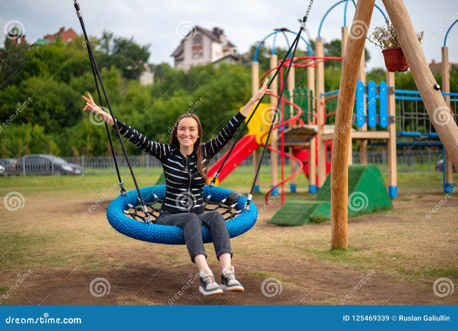 Jonge gelukkige vrouw bij het hangen van schommeling in Park het glimlachen handen omhoog, concept vrijheid, weekend, kinderjaren
