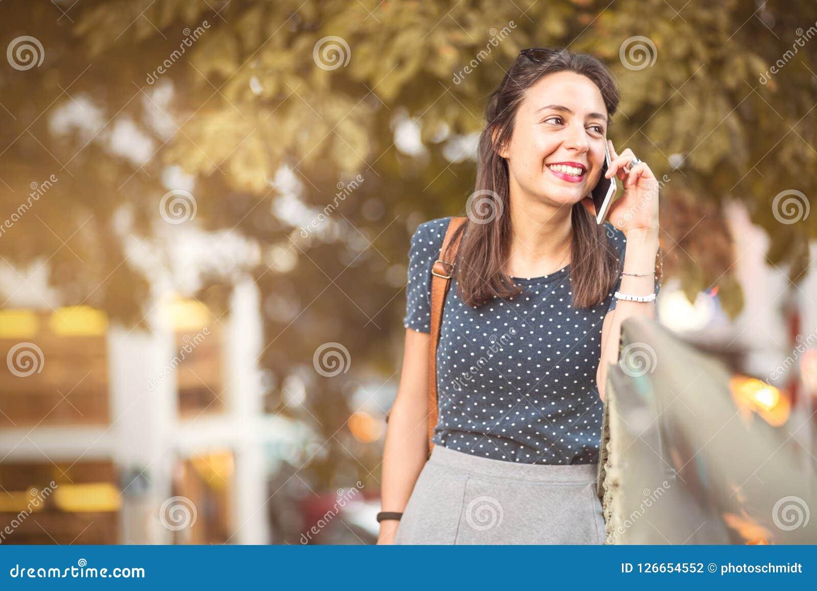 Jonge, gelukkige vrouw die aan een celtelefoongesprek luisteren