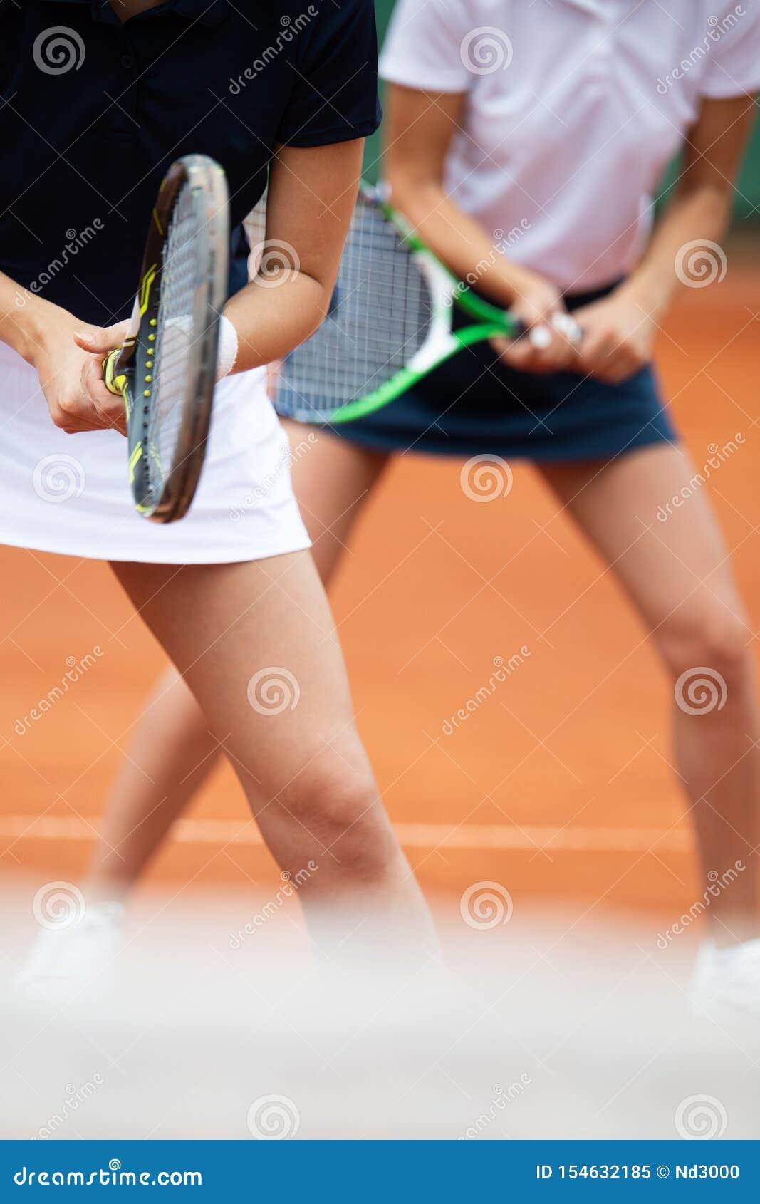 Jonge gelukkige vrouwenvrienden die tennis spelen bij tennisbaan