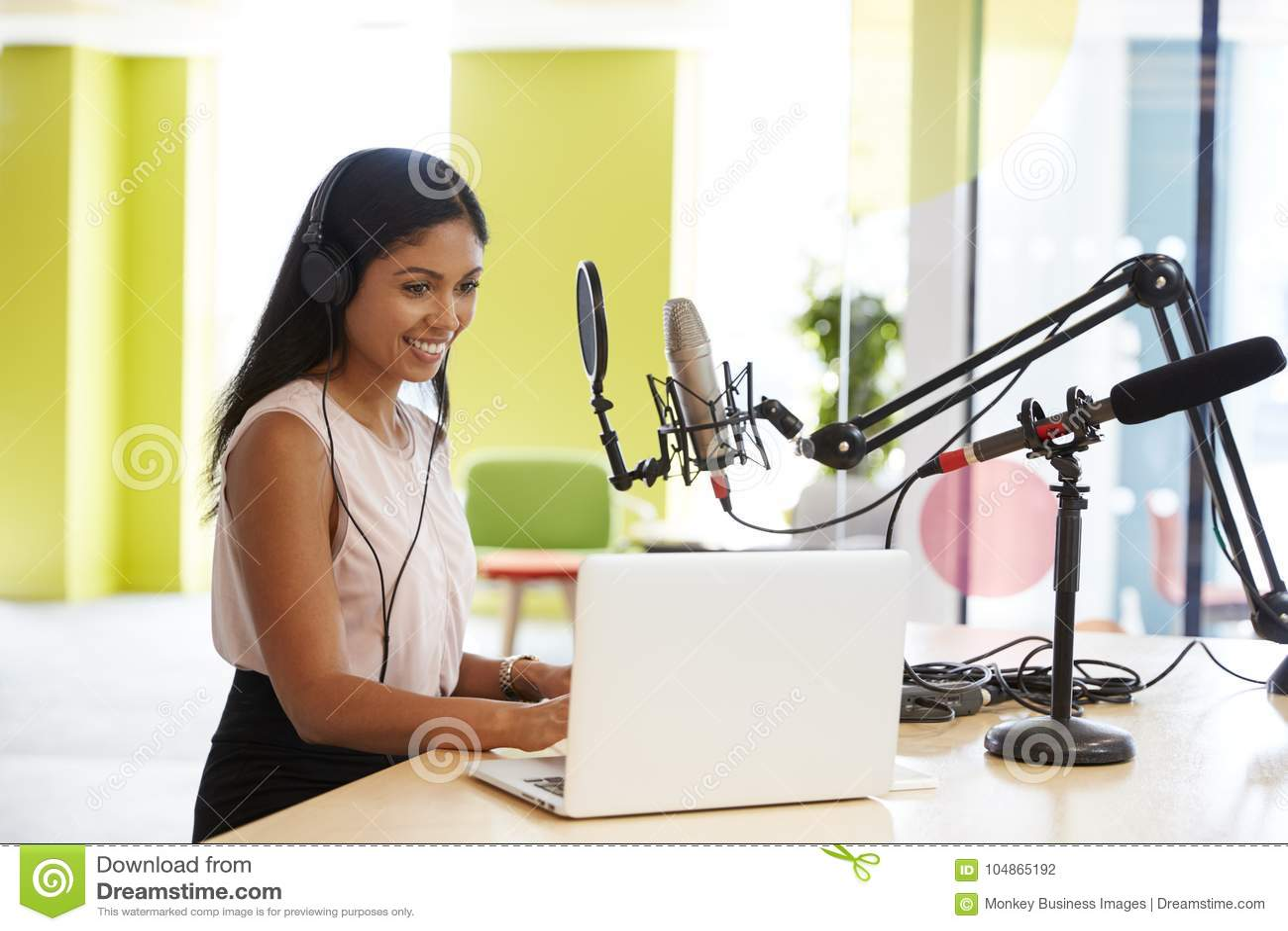 Jonge gemengde rasvrouw die een podcast in een studio registreren
