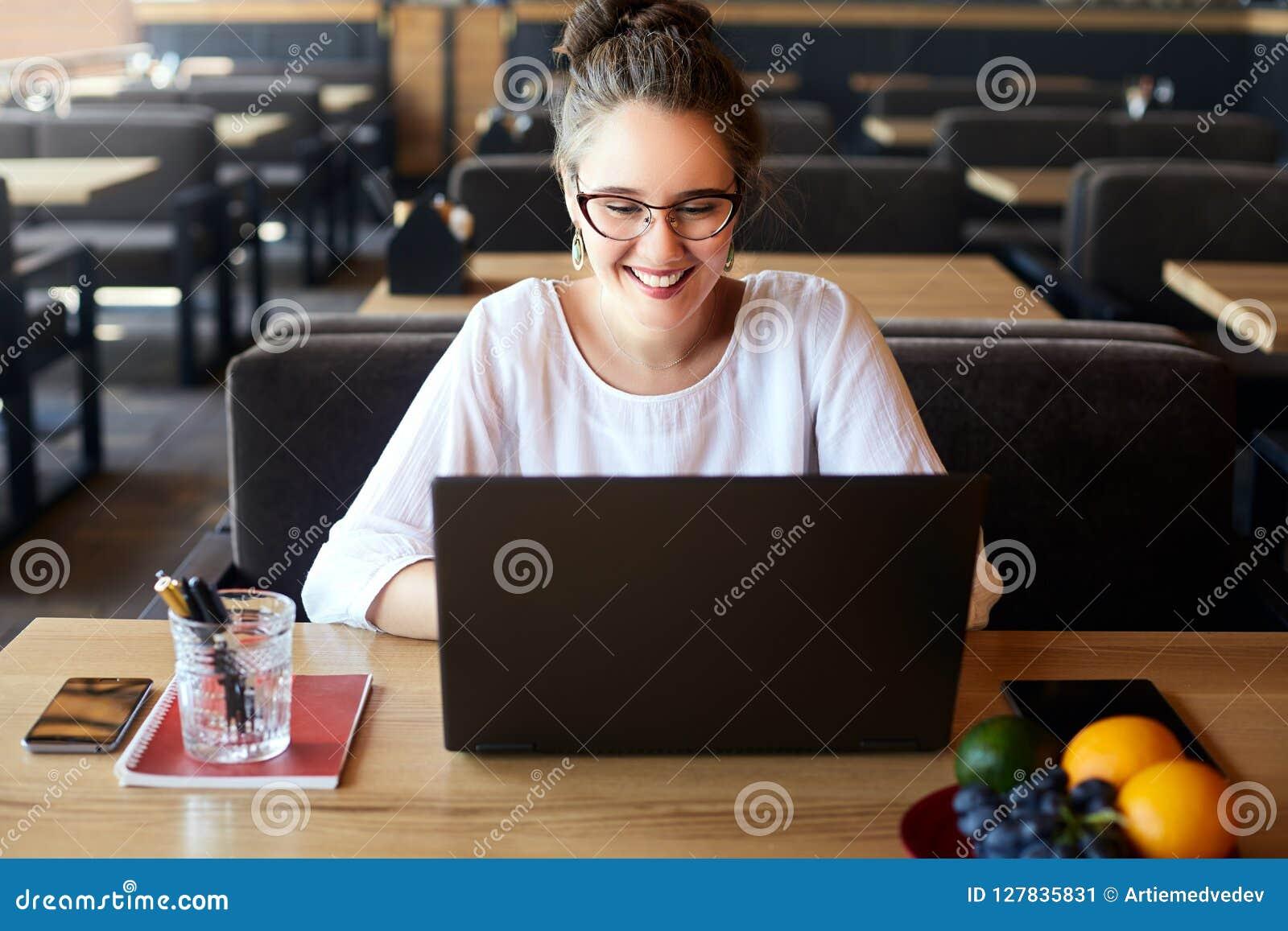 Jonge gemengde rasvrouw die met laptop in koffie werken Aziatisch Kaukasisch wijfje die gebruikend Internet bestuderen Het bedrij