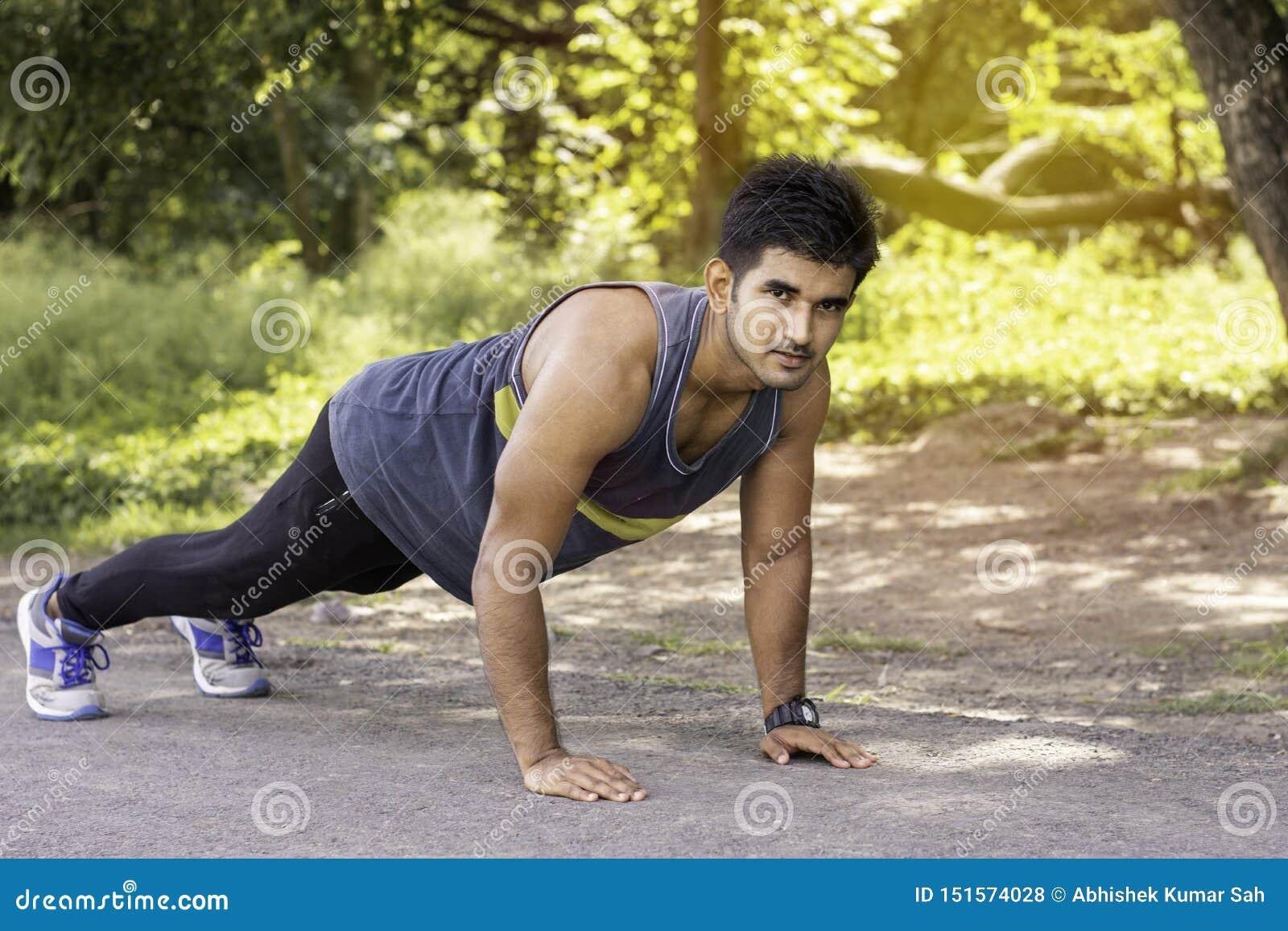 Jonge geschikte Kaukasische mens met spierlichaam die opdrukoefeningen in openlucht op zonnige de zomerdag doen