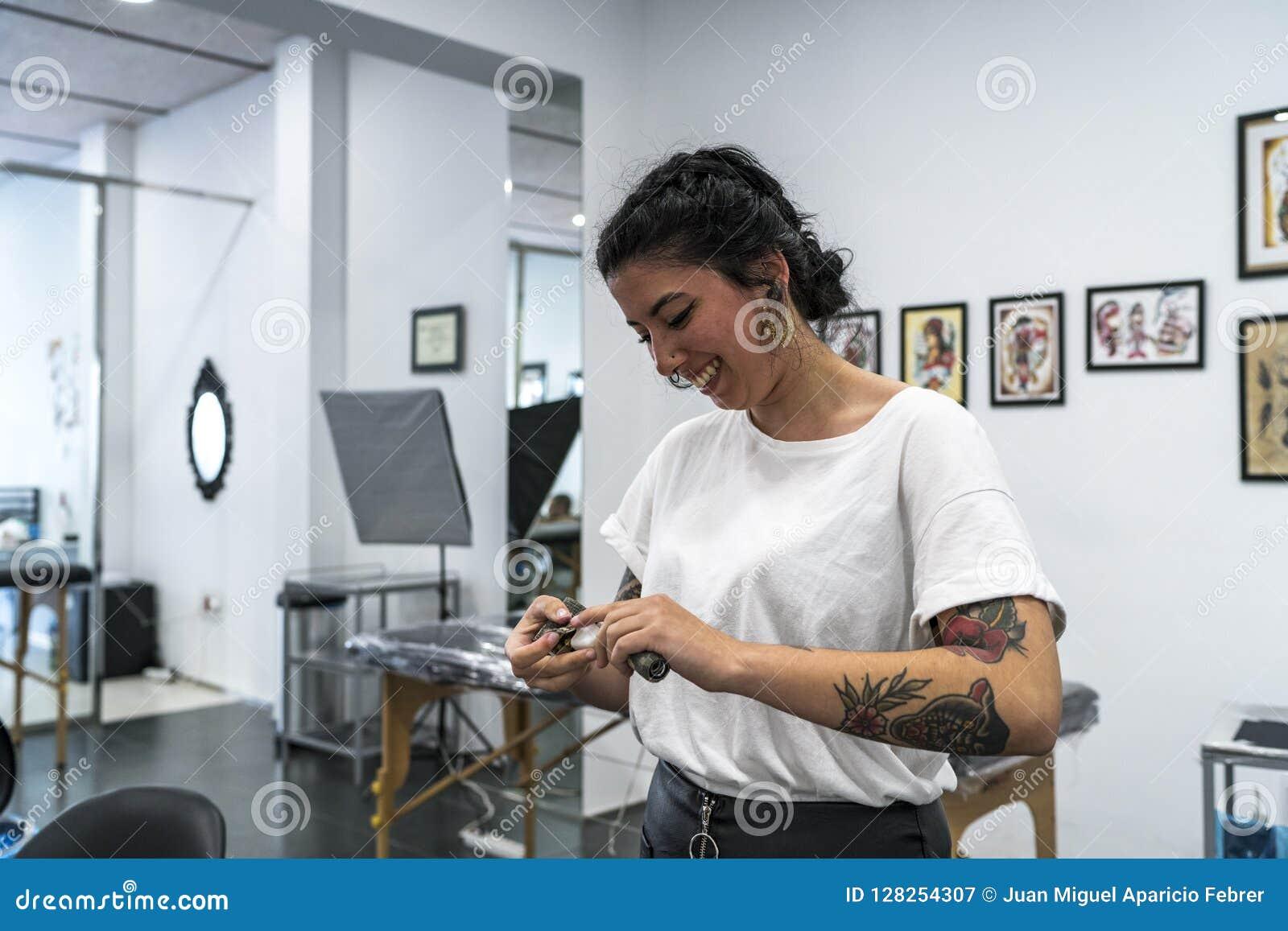 Jonge getatoeeerde vrouw het voorbereiden van de tatoegeringsmachine