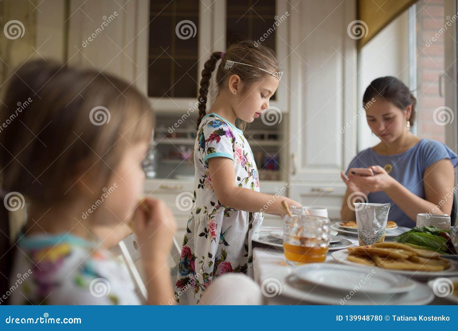 Jonge gevende moeder en haar twee kleine dochters die pannekoeken met honing eten bij het ontbijt in de comfortabele keuken