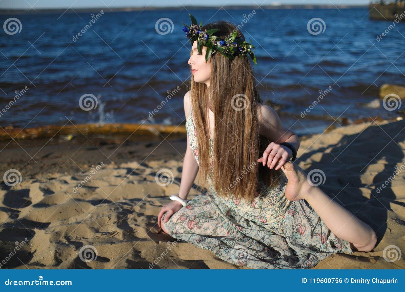 Jonge gezonde vrouw het praktizeren yoga op het strand bij zonsopgang