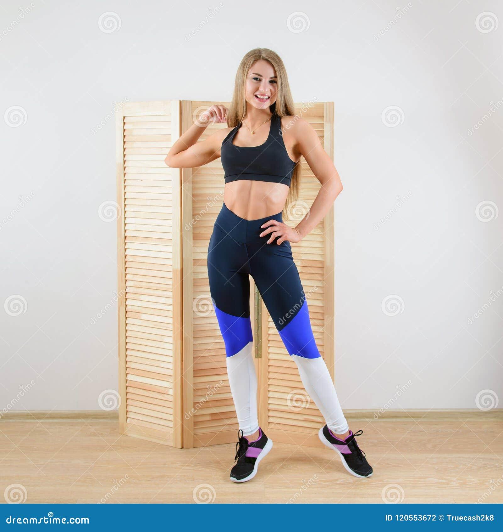 Jonge gezonde vrouw in sportkleding het stellen Gelukkig mooi meisje die bij camera glimlachen