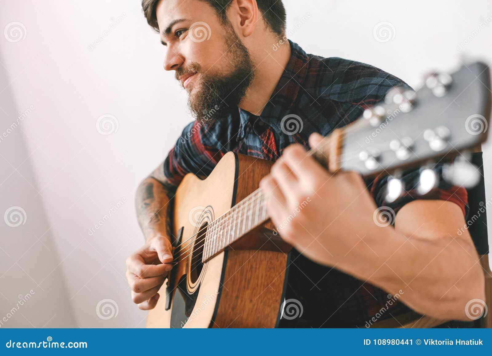 Jonge gitarist hipster thuis het spelen gitaar die bemiddelaarsclose-up gebruiken