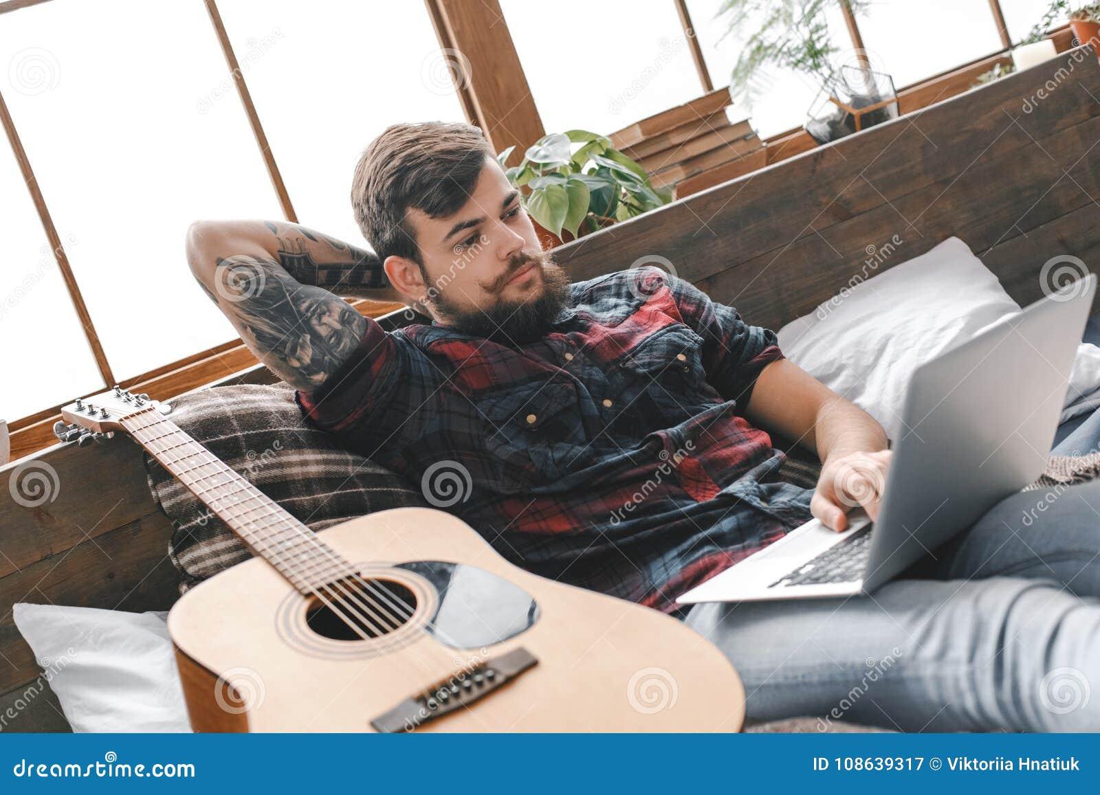 Jonge gitarist hipster thuis met gitaar in slaapkamer die Internet doorbladeren