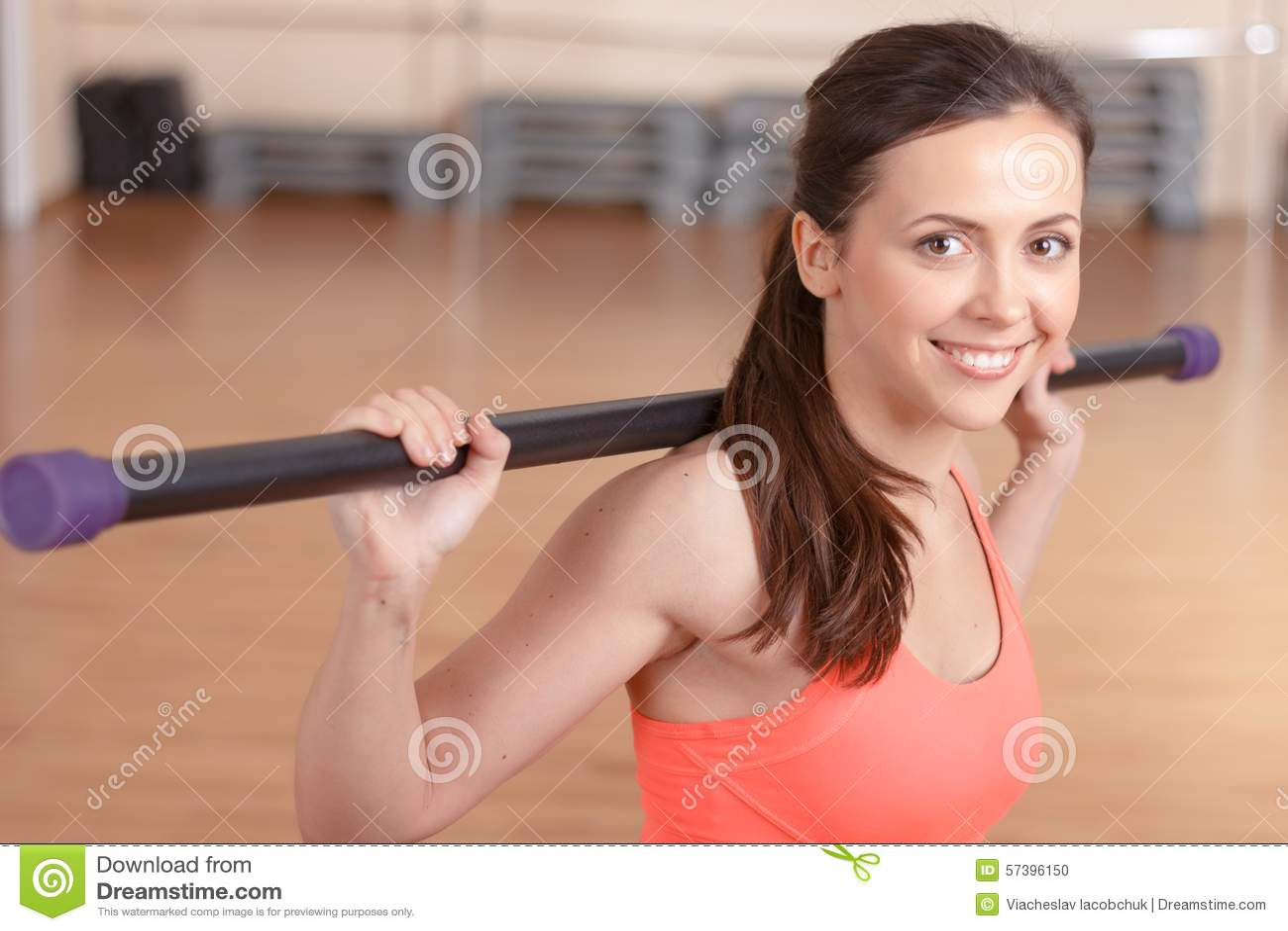 Jonge glimlachende vrouw die stokoefeningen doen