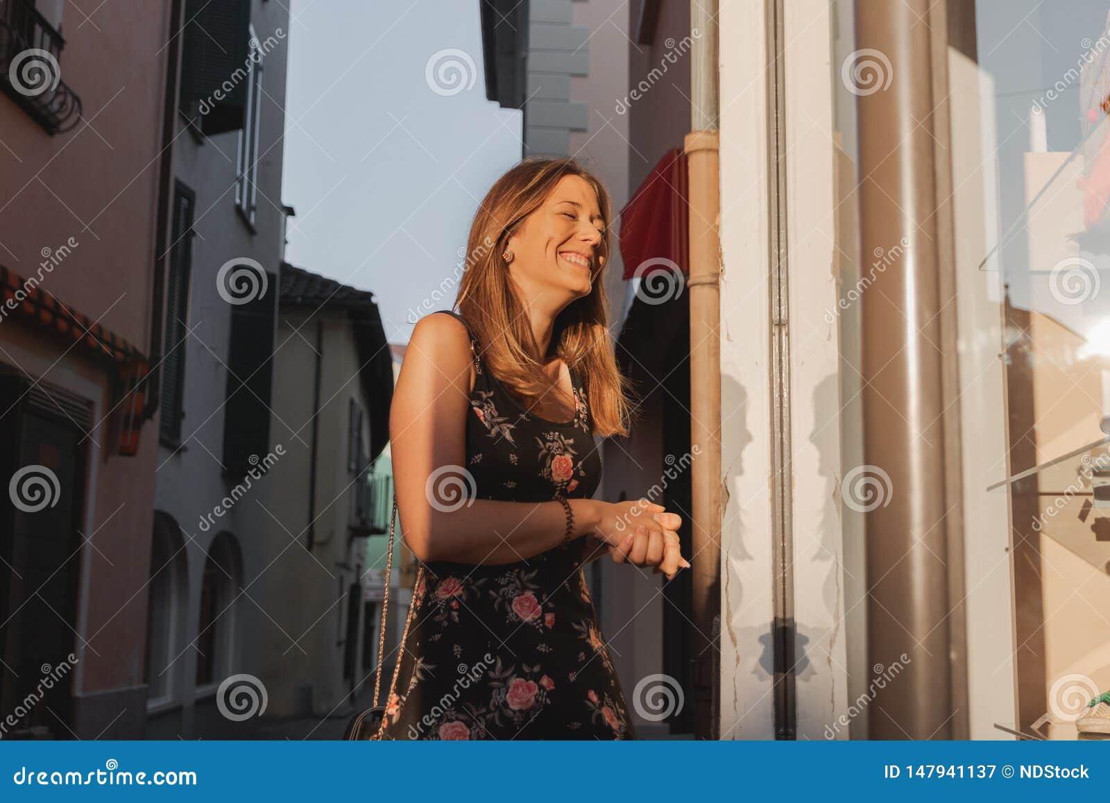 Jonge glimlachende vrouw die winkelvenster bekijken in een steeg in ascona