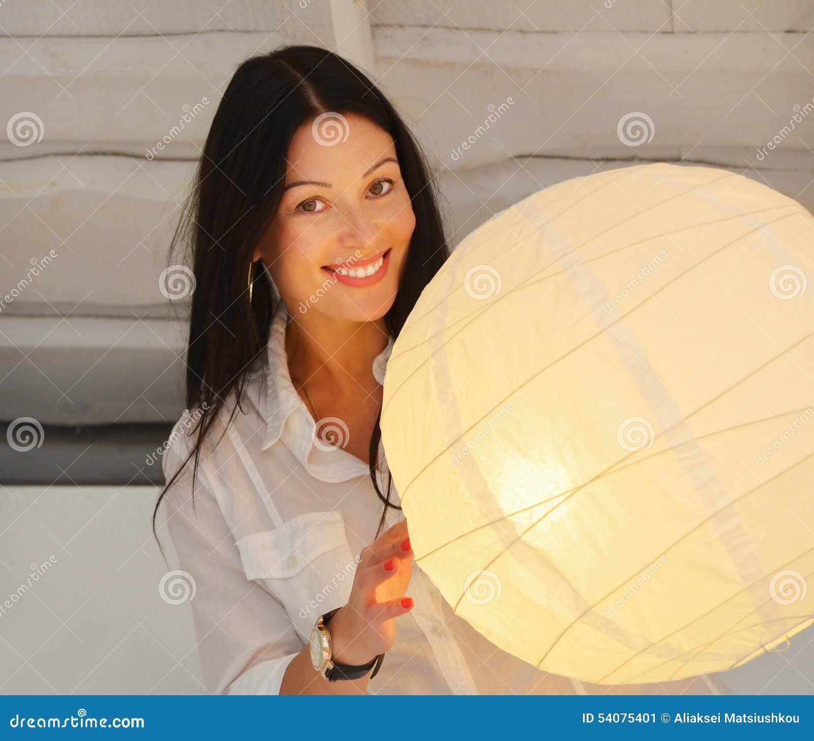 Jonge glimlachende vrouw die zich dichtbij lamp, in het huis bevinden