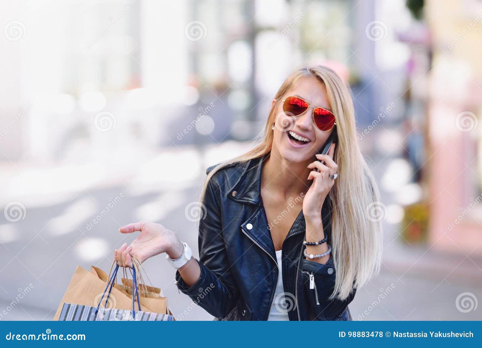 Jonge glimlachende vrouw met het winkelen zakkenbespreking door cellulaire telefoon