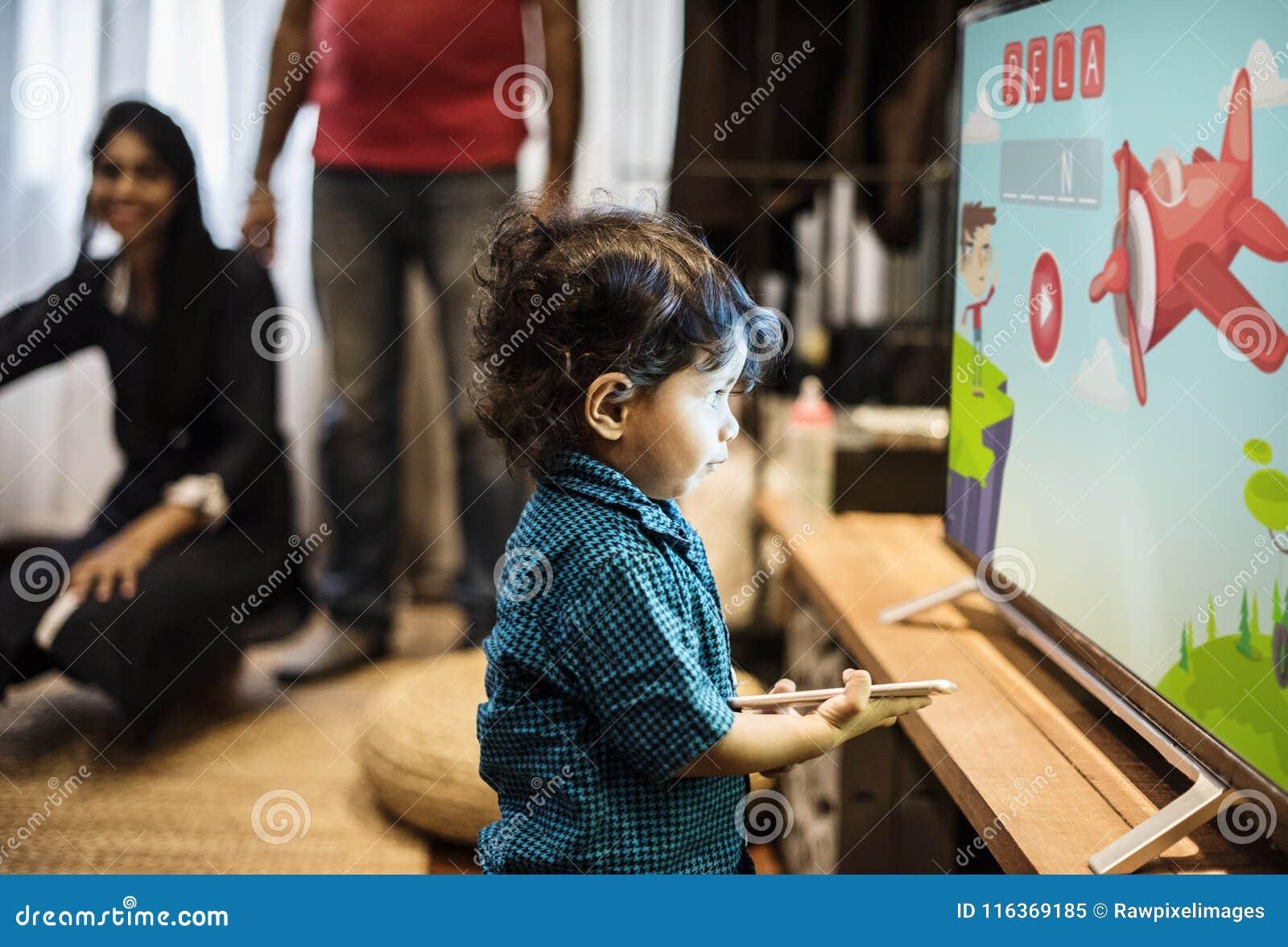 Jonge Indische jongen het letten op televisie
