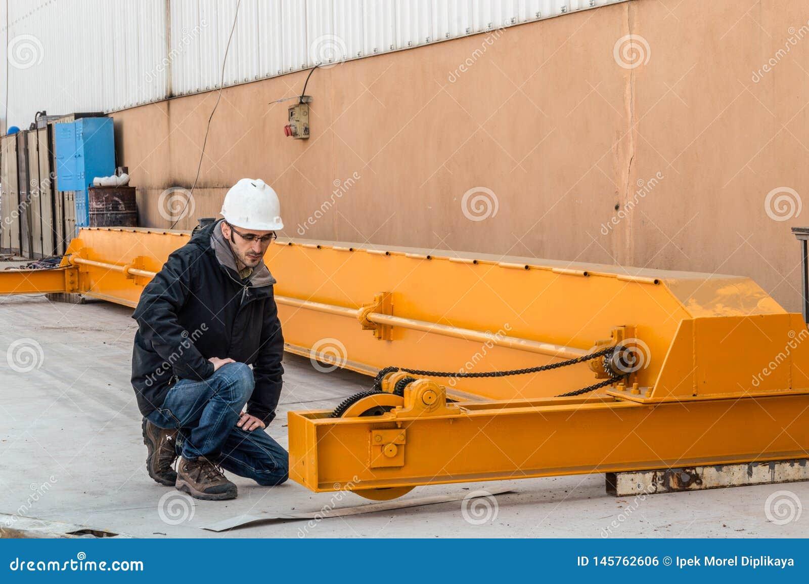 Jonge ingenieur die de brugkraan in de fabriek controleren