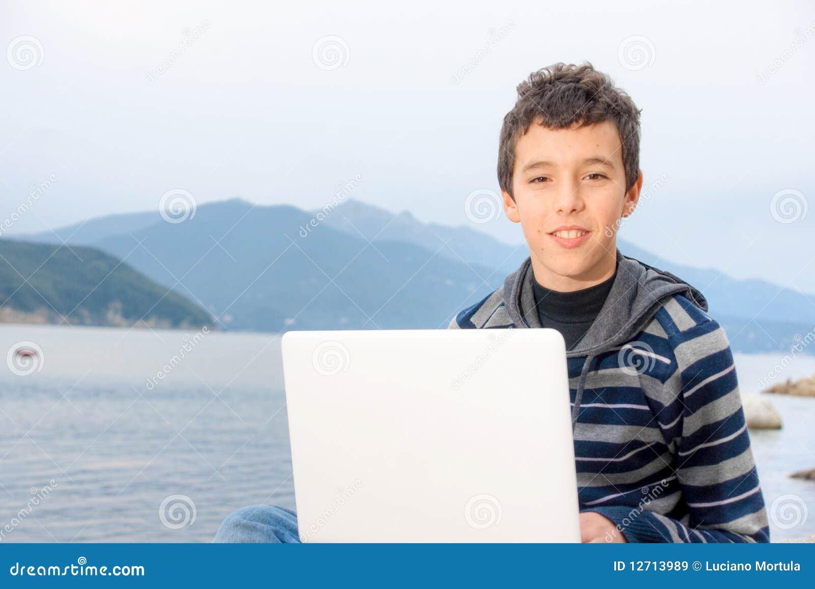 Jonge Jongen die laptop buiten met behulp van.