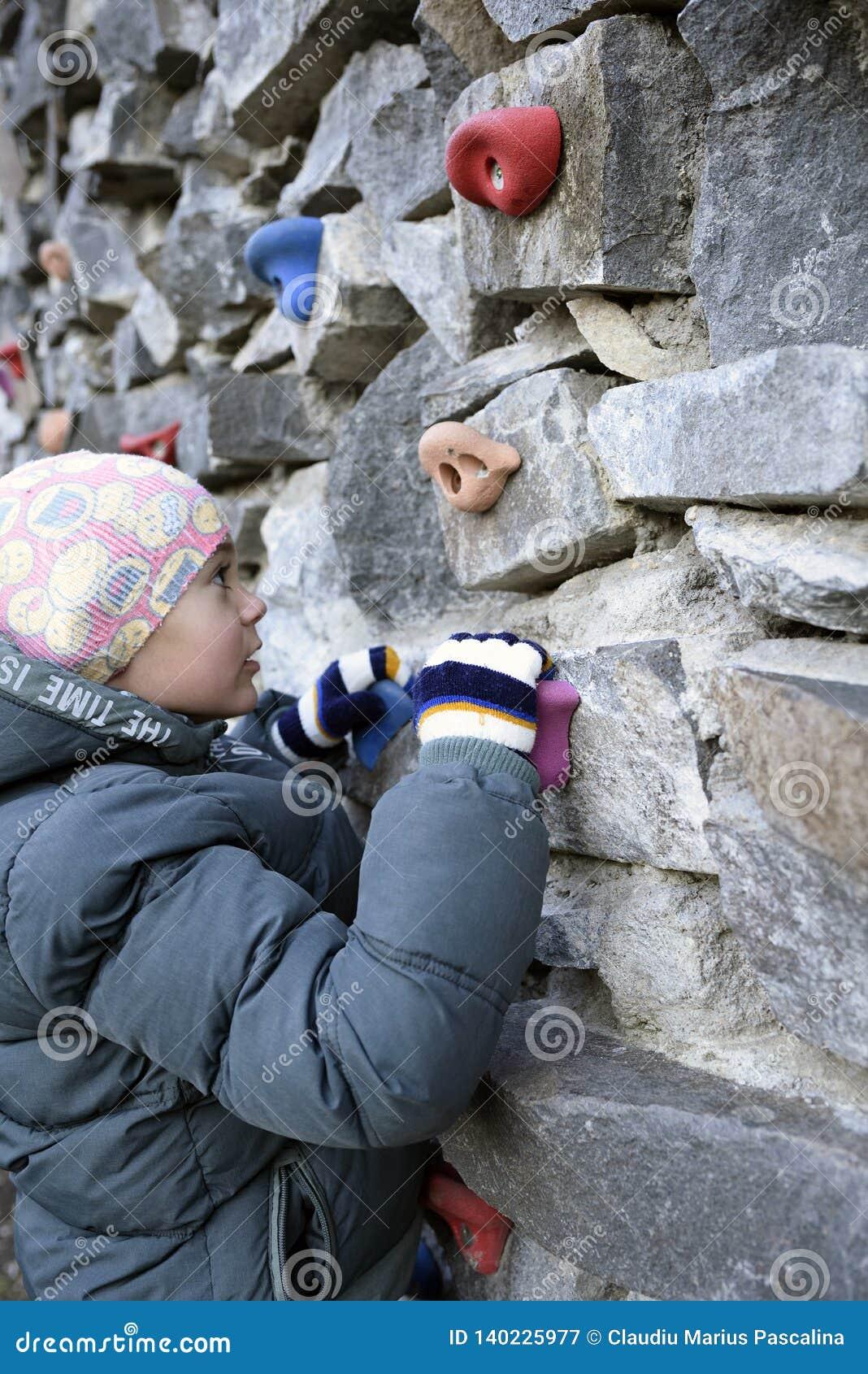 Jonge jongen die op de muur beklimmen