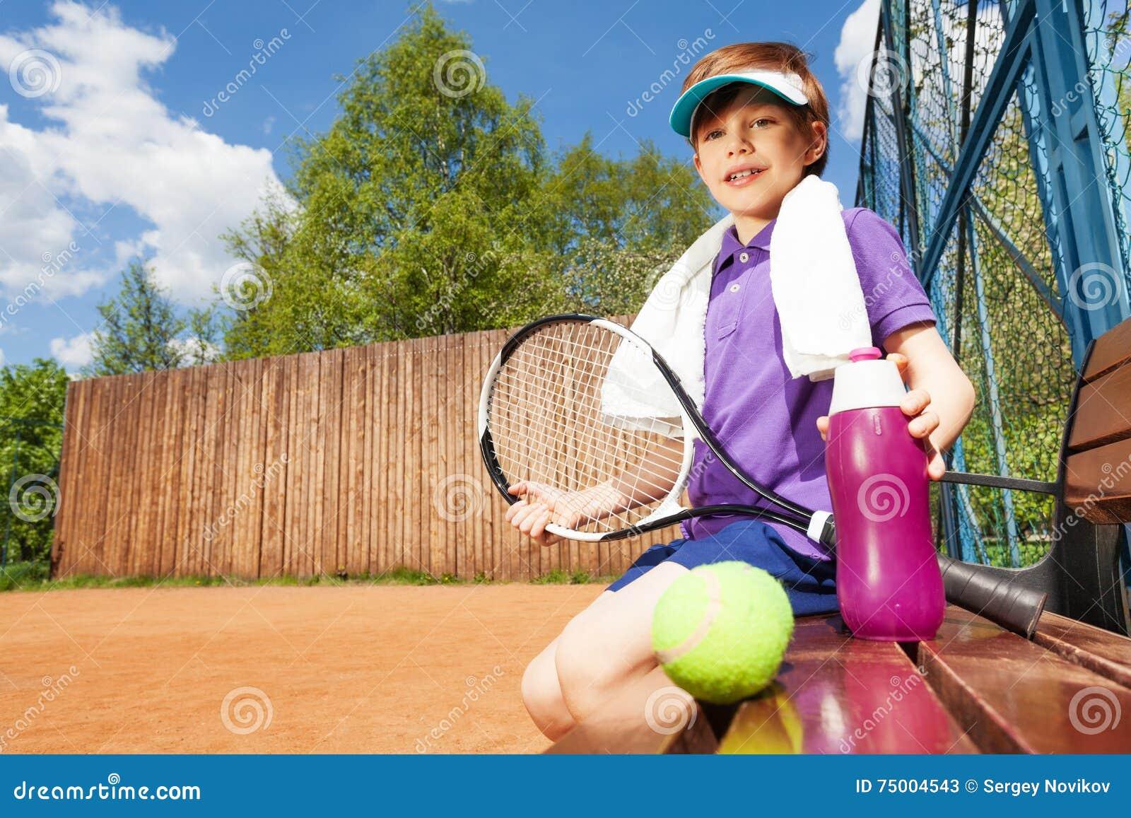 Jonge jongen die rust na het spelen van tennis hebben