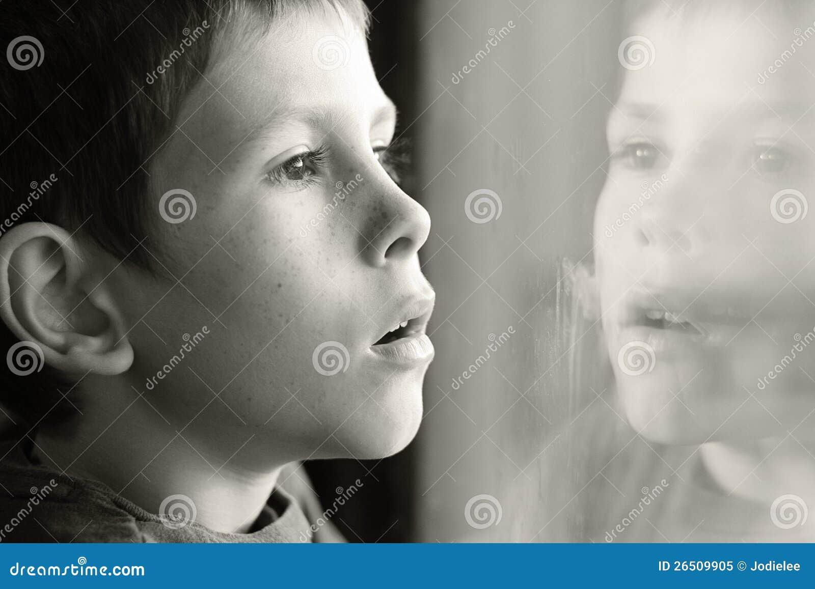 Jonge jongen in gedachte met vensterbezinning