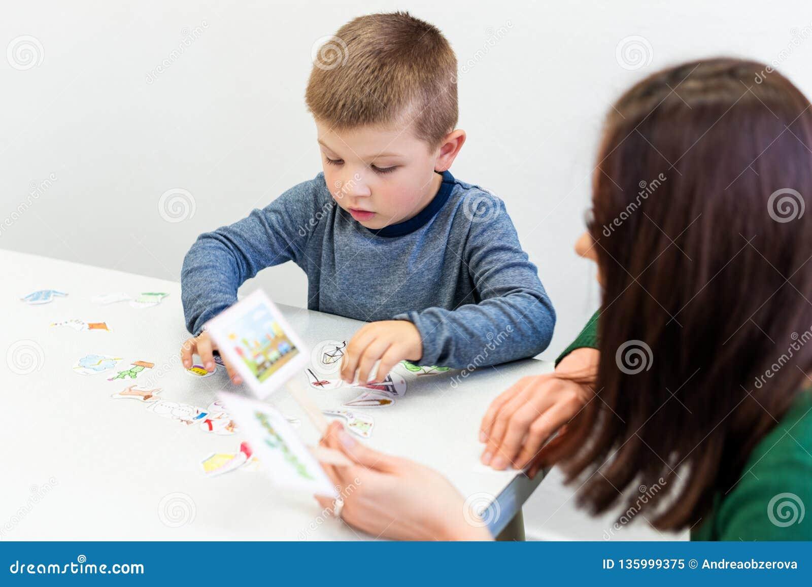 Jonge jongen in logopediebureau Kleuter die correcte uitspraak met toespraaktherapeut Child Occupational Therapy uitoefenen