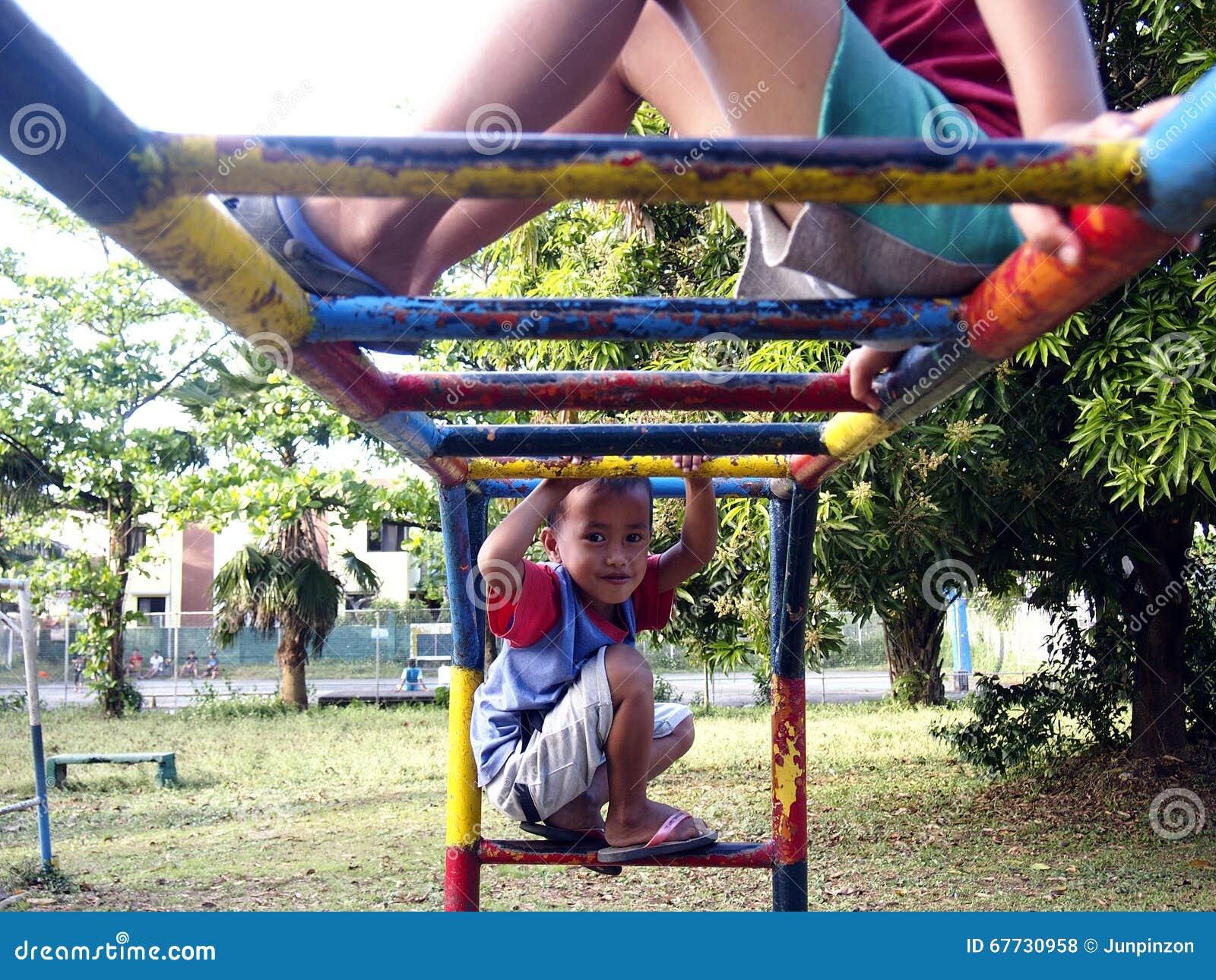 Jonge jongens en meisjes die bij een speelplaats in Antipolo-Stad, Filippijnen spelen