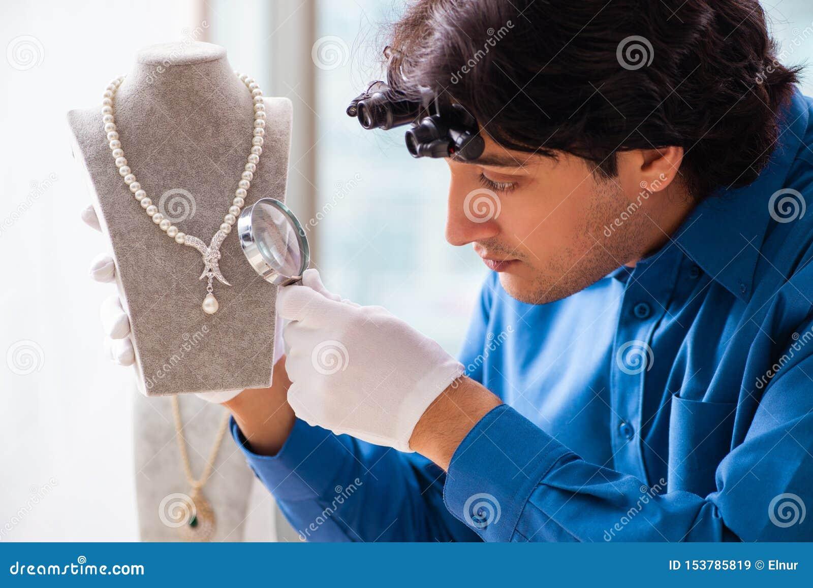 Jonge juwelier die in zijn workshop werkt