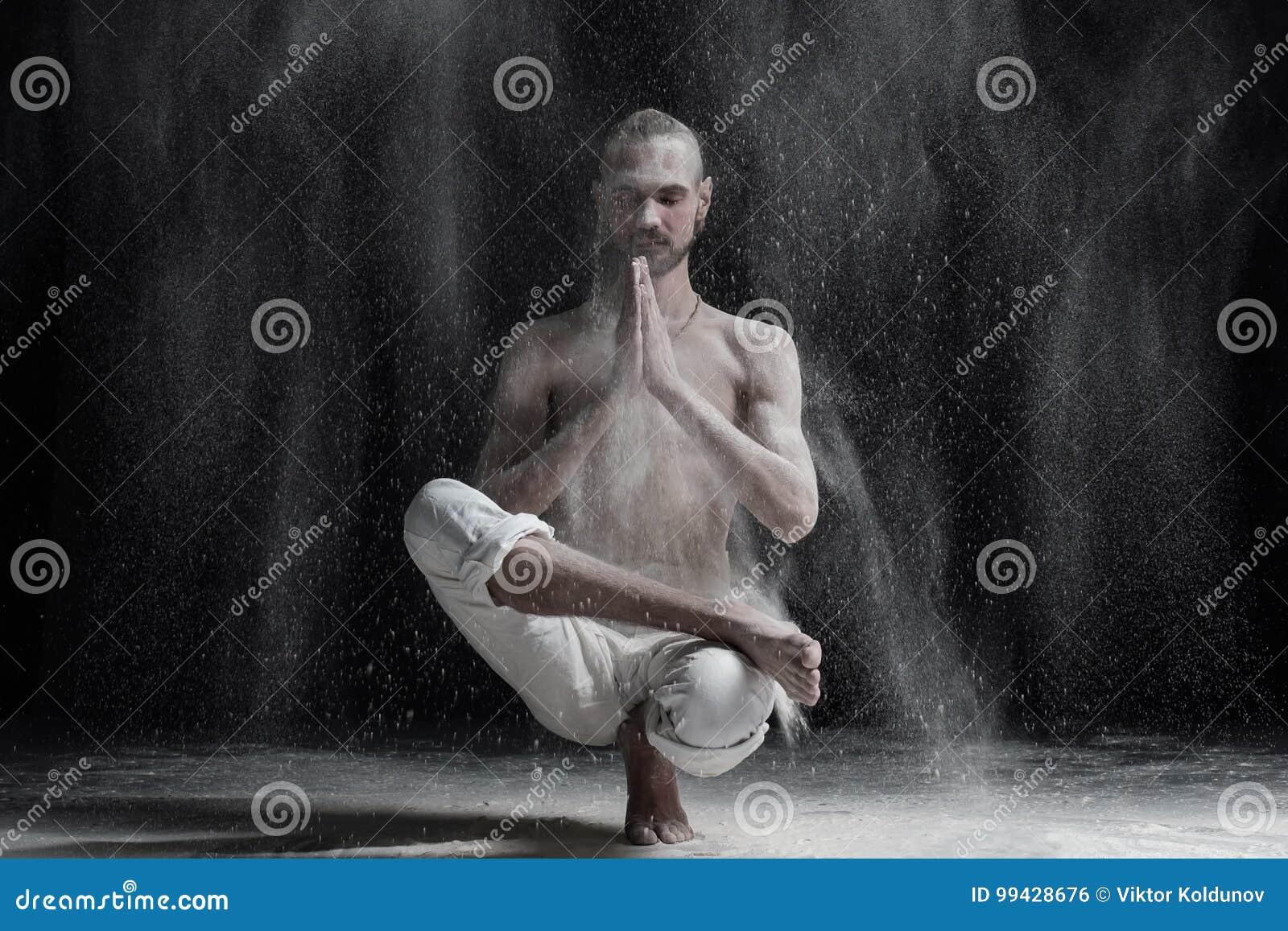 Jonge kalme Kaukasische mens die yoga of pilates oefening doen Zittend in hurkende positie, Halve Lotus Toe Balance