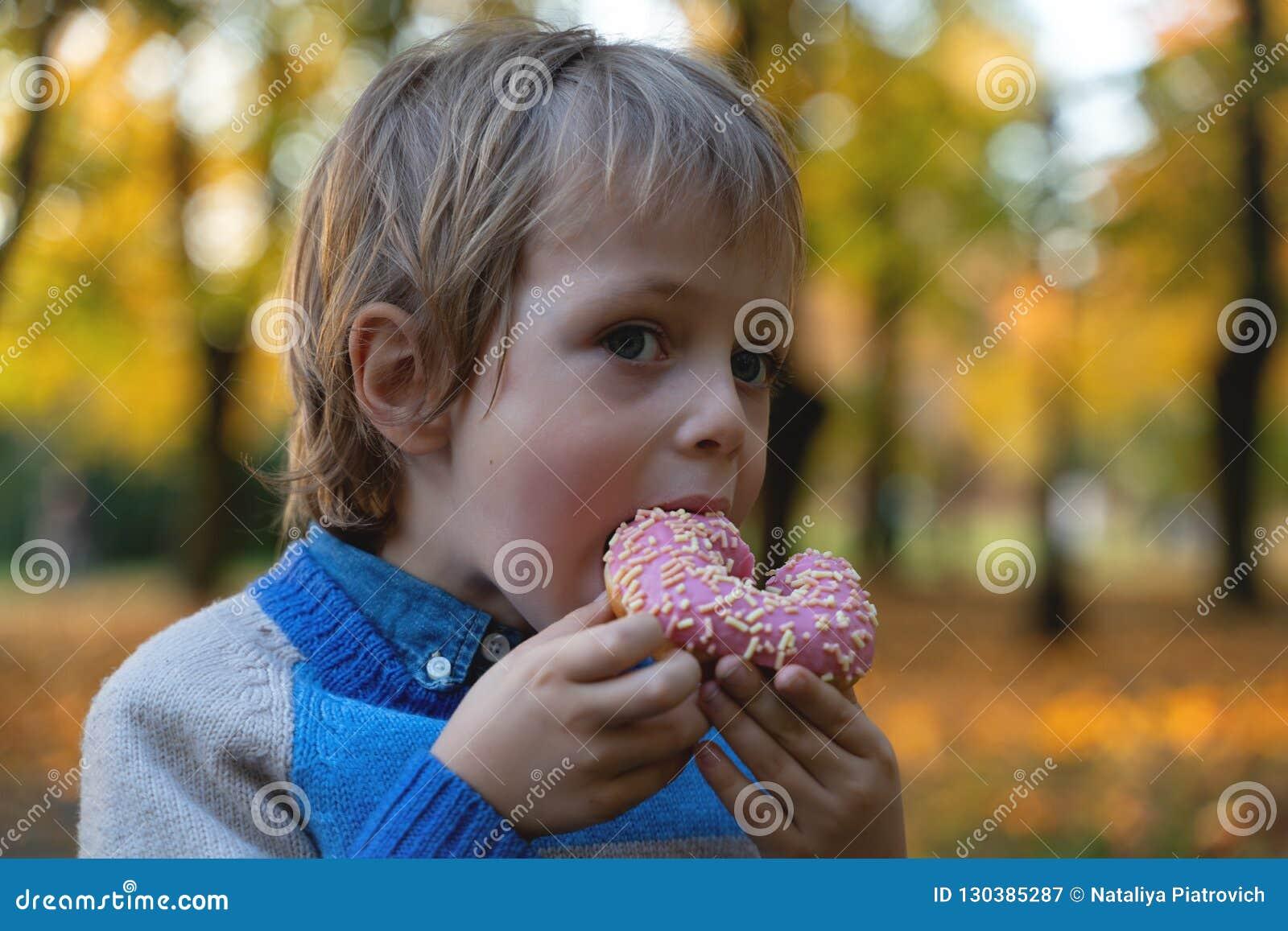 Jonge Kaukasische jongen 5 van de oude het eten doughnut in openlucht jaar close-up Kinderjaren