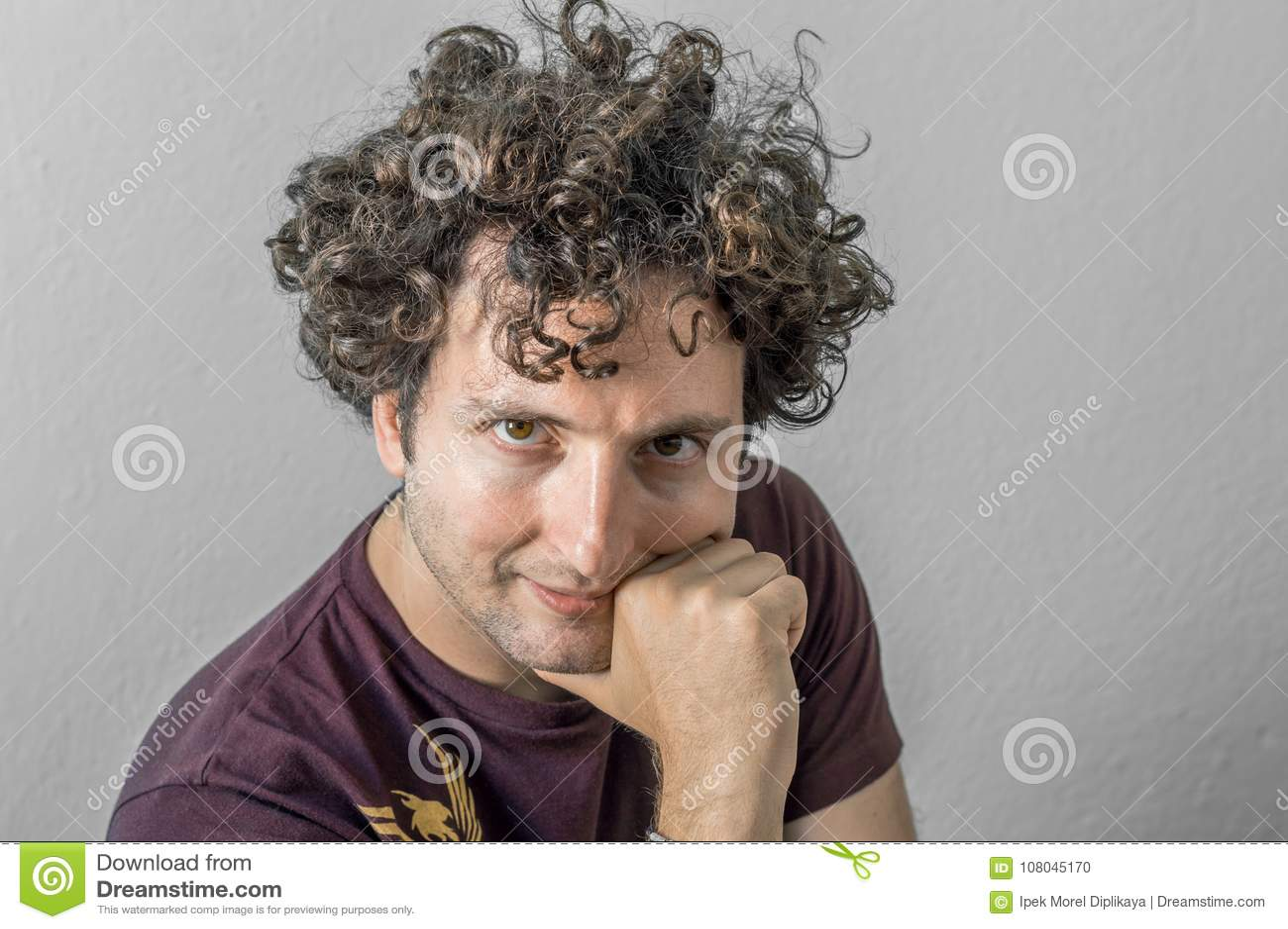 Jonge Kaukasische mens die met krullend haar aan de camera op witte achtergrond kijken
