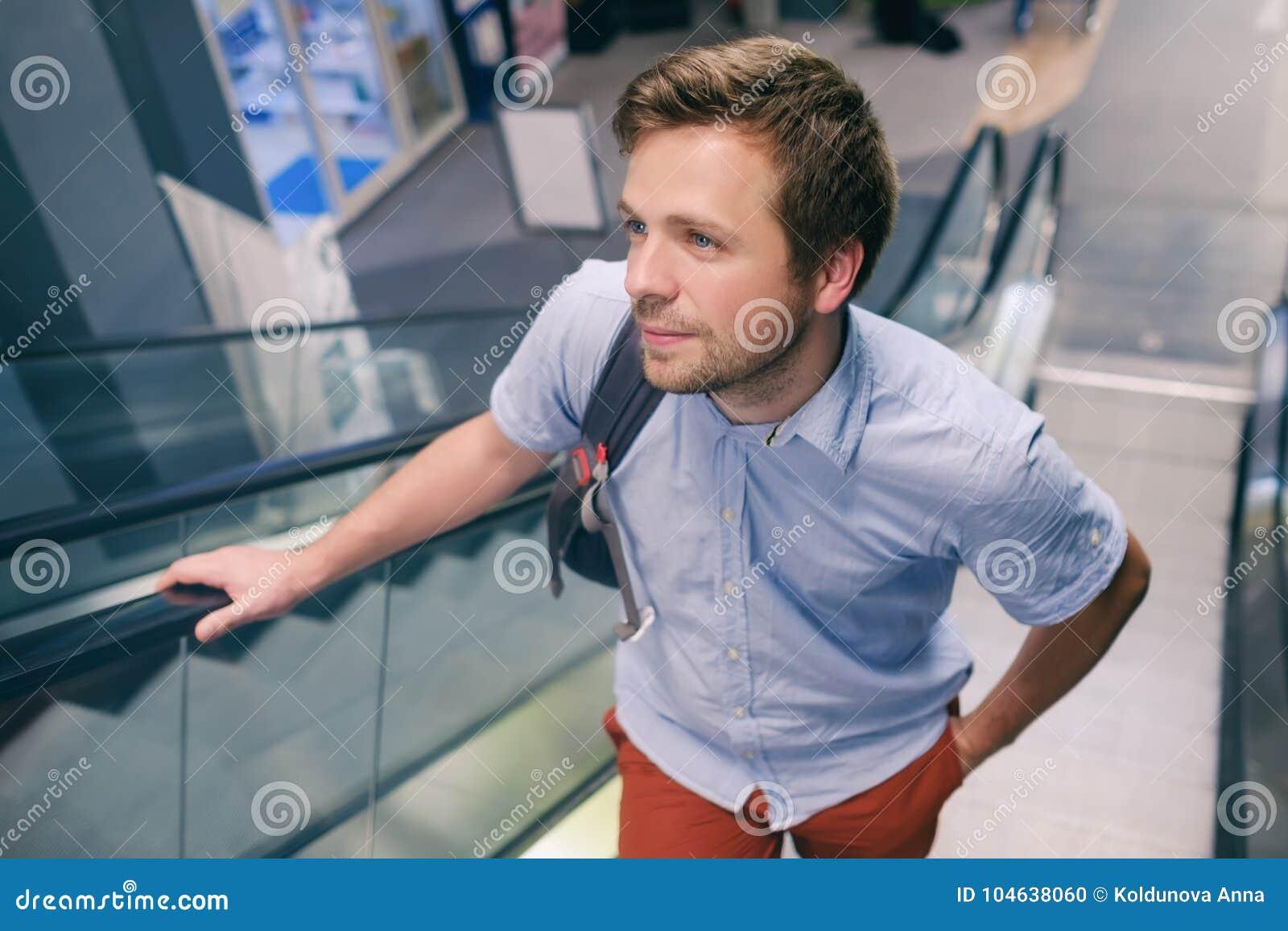 Download Jonge Kaukasische Mens Die Zich Omhoog Op Een Roltrap Bij De Luchthaven Bewegen Stock Foto - Afbeelding bestaande uit modieus, levensstijl: 104638060
