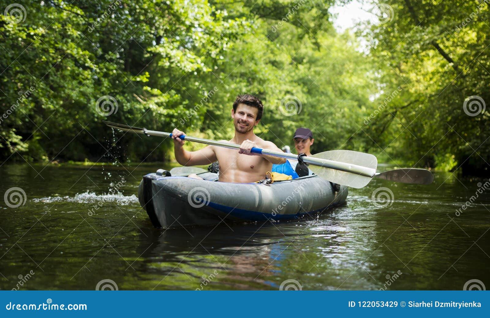 Jonge kerels in boot met roeispanen op rivier tegen achtergrond van groene bomen over water Kayakers in kajak
