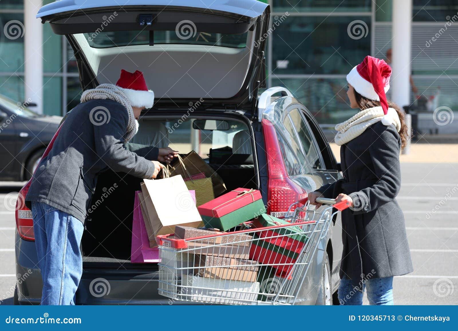 Jonge Kerstmisaankopen van de paarlading in autoboomstam op winkelcomplexparkeren