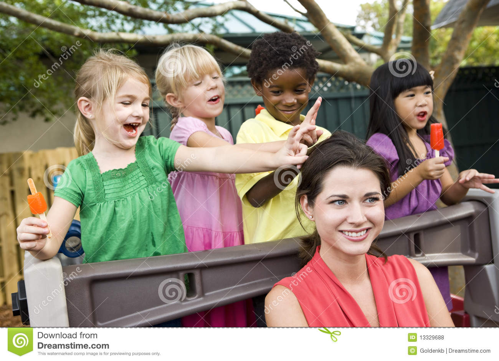 Jonge kinderen die in opvang met leraar spelen