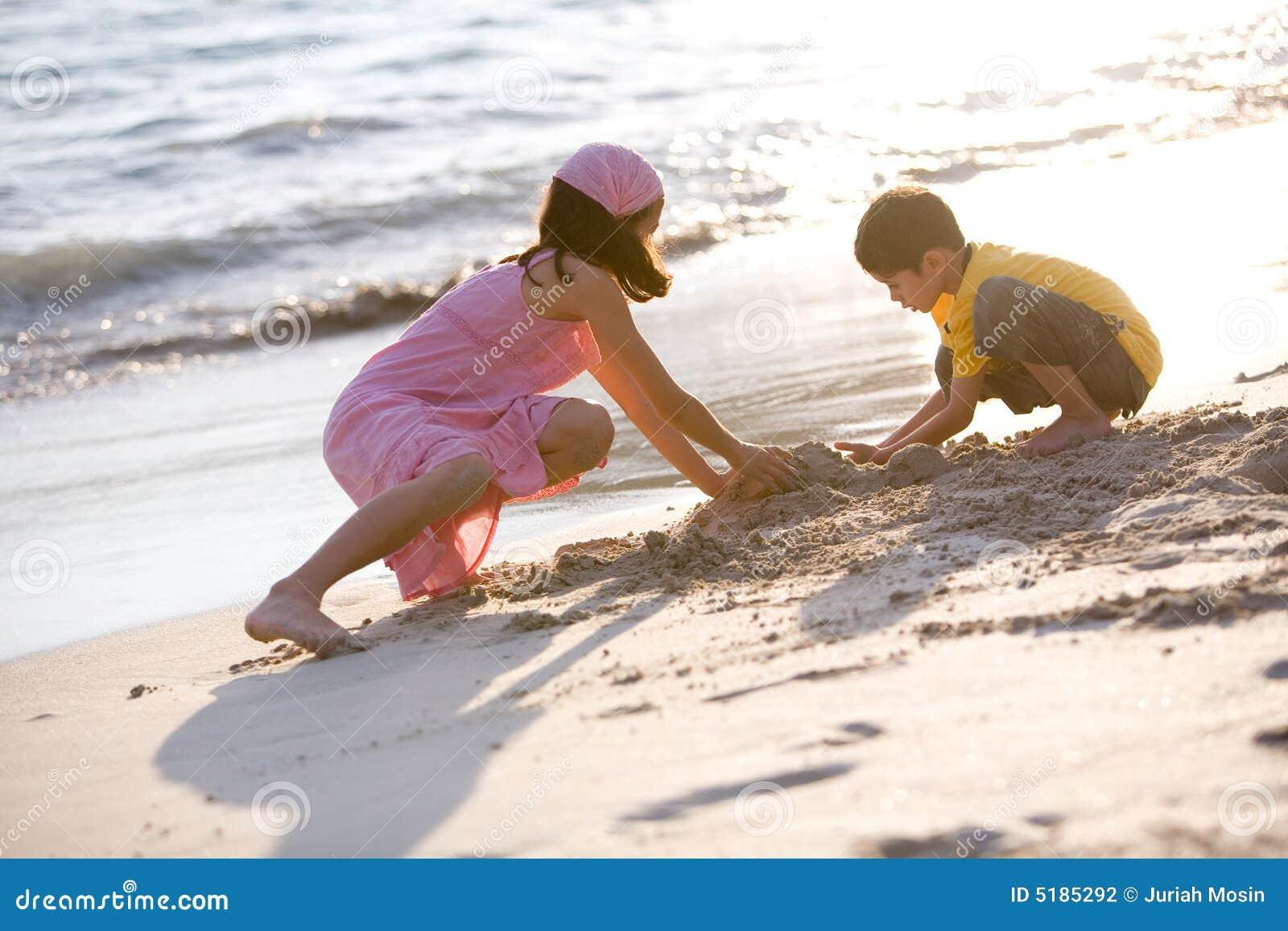Jonge kinderen die zandkasteel maken