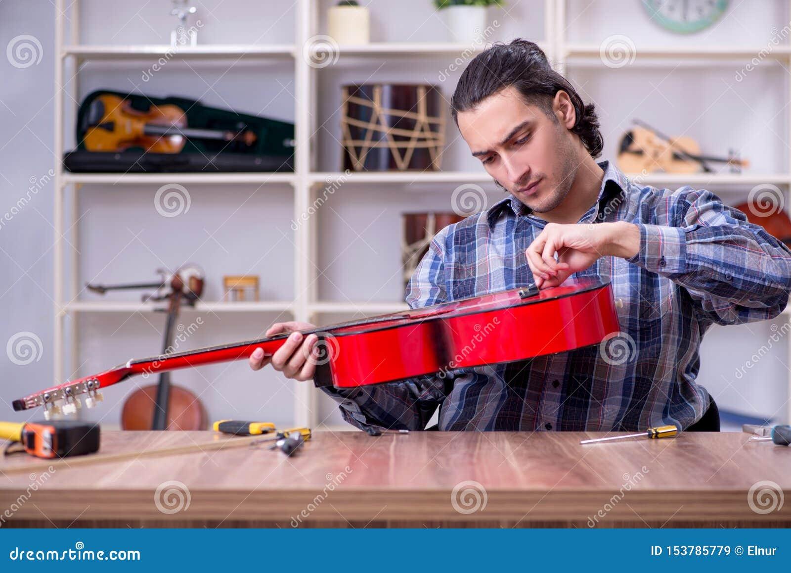 Jonge knappe hersteller die gitaar herstellen